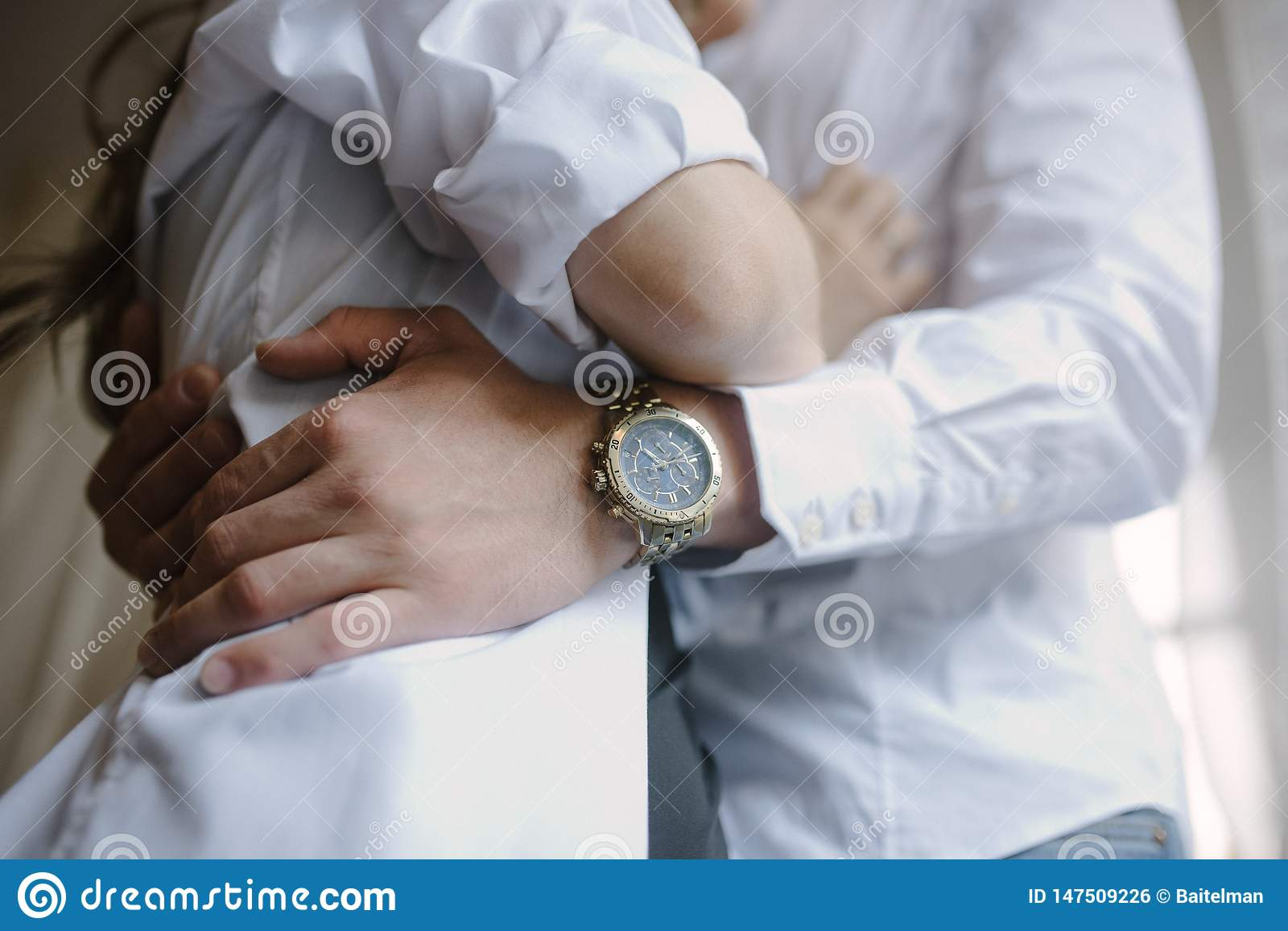 The groom in a suit hugs the bride in a wedding dress