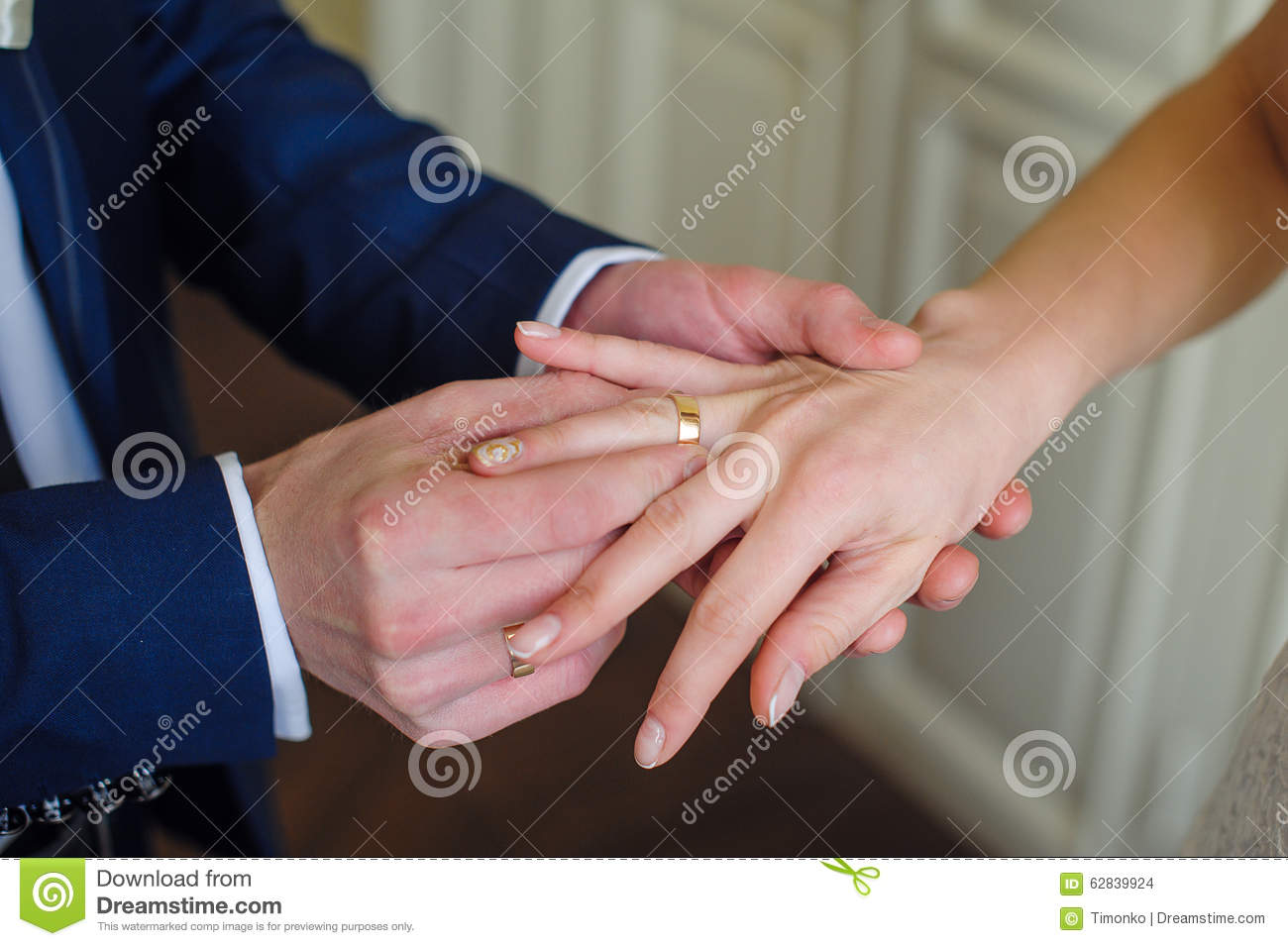 Groom Wears Bride A Gold Ring On Her Finger Stock Photo - Image of ...