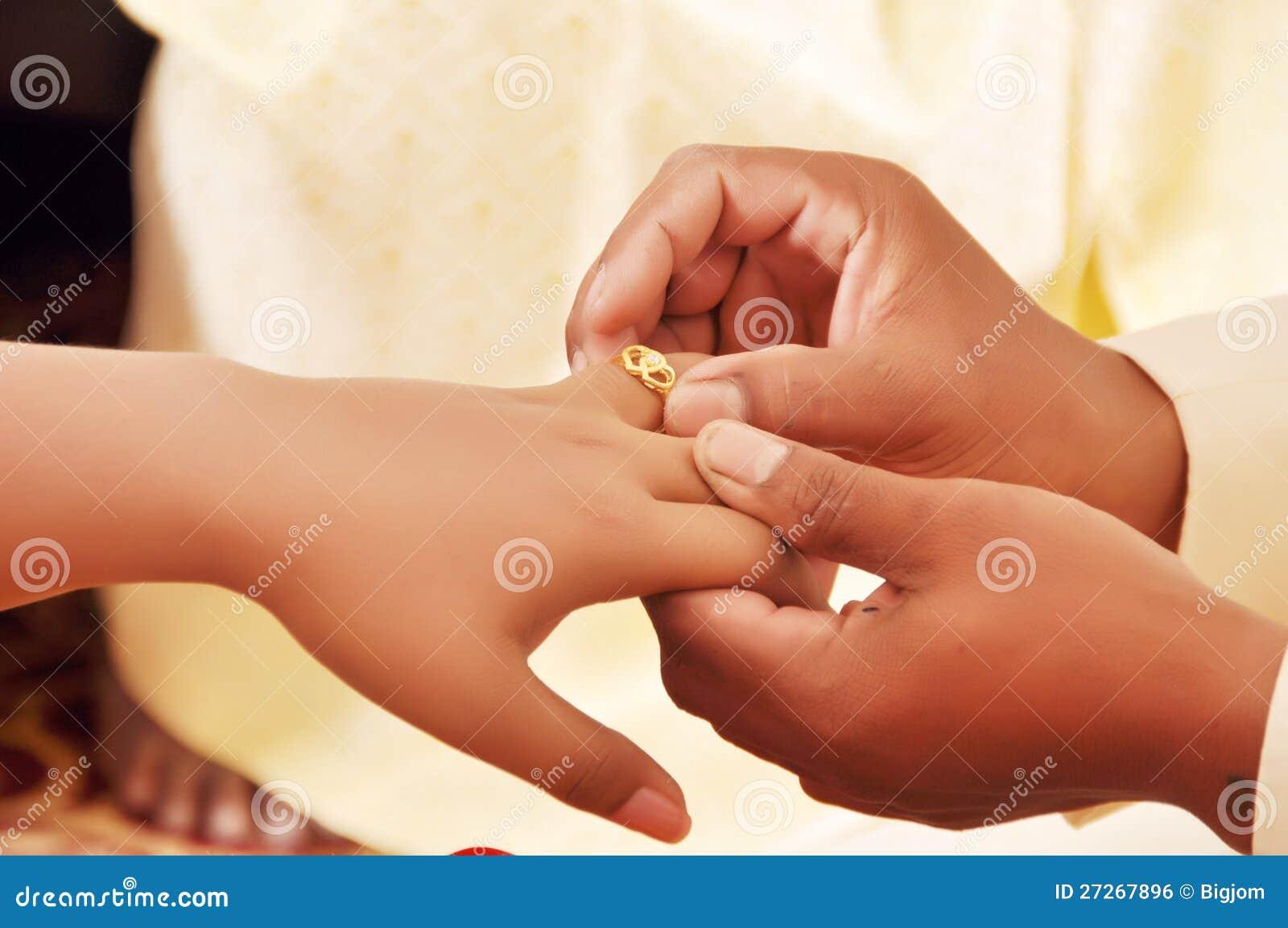 Groom Wears A Diamond Ring Onto The Brides Hand Stock Photo