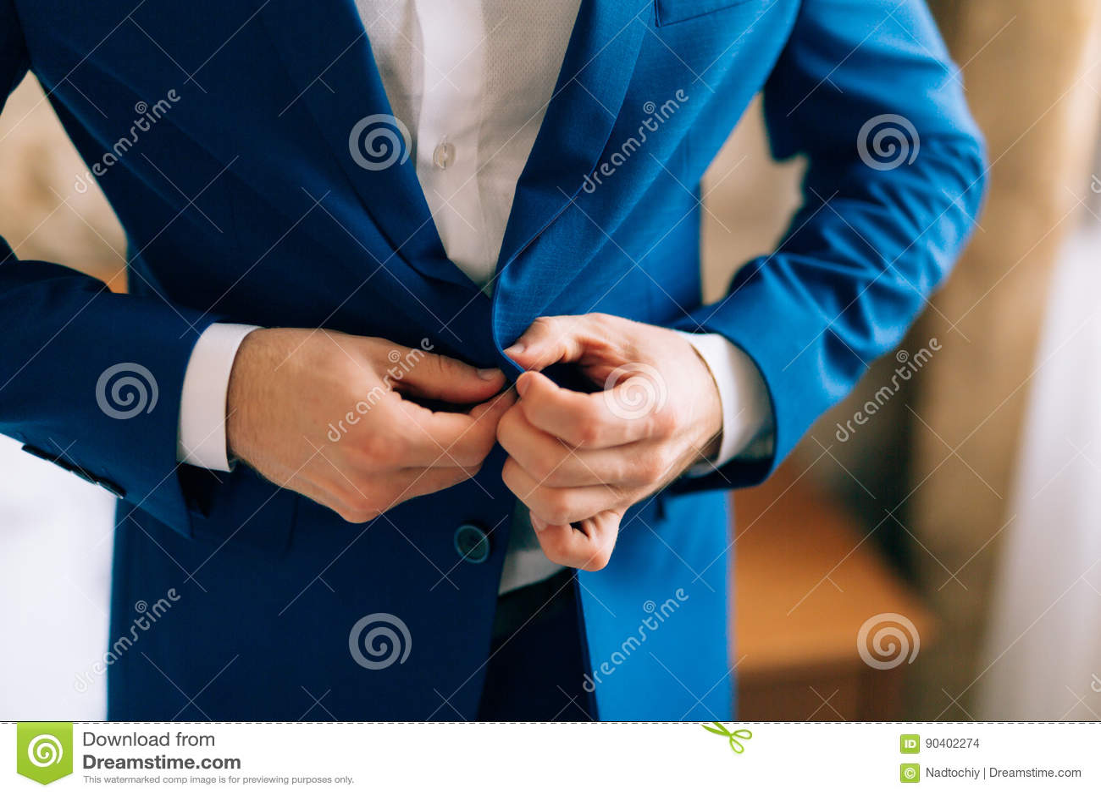 The groom zips up the jacket