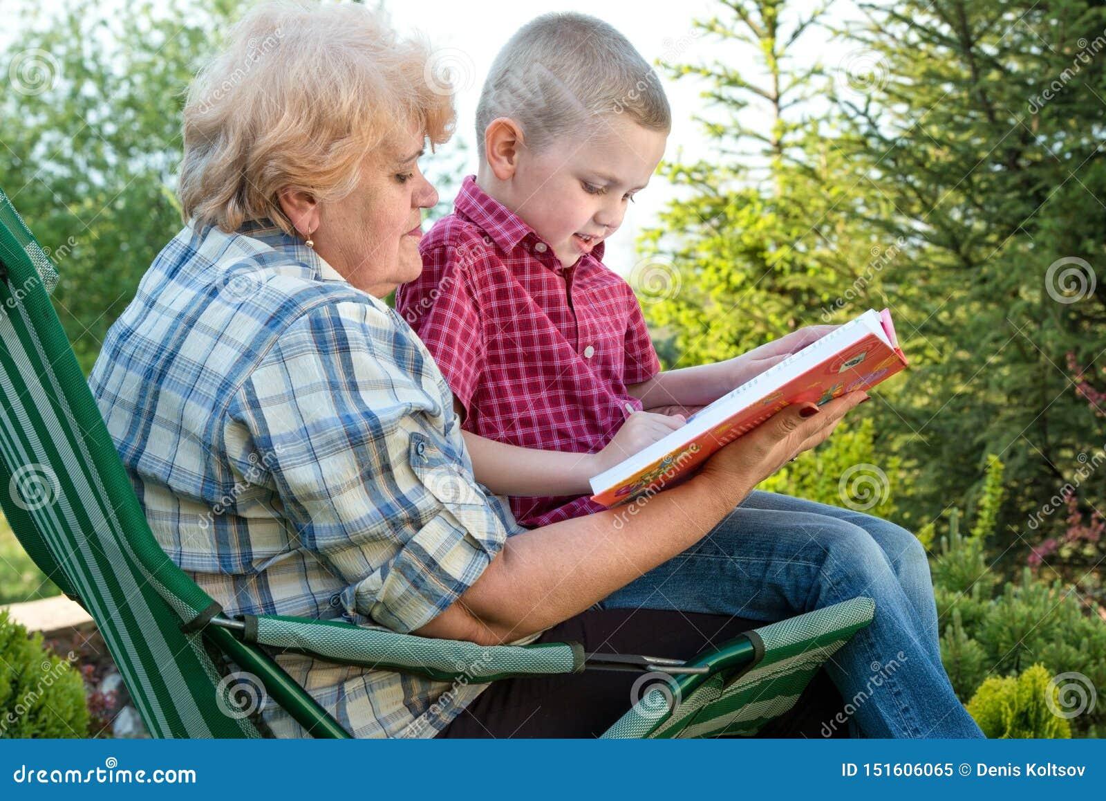 Grootmoeder en kleinzoon die een boek in openlucht lezen Familievakantie met mijn grootmoeder