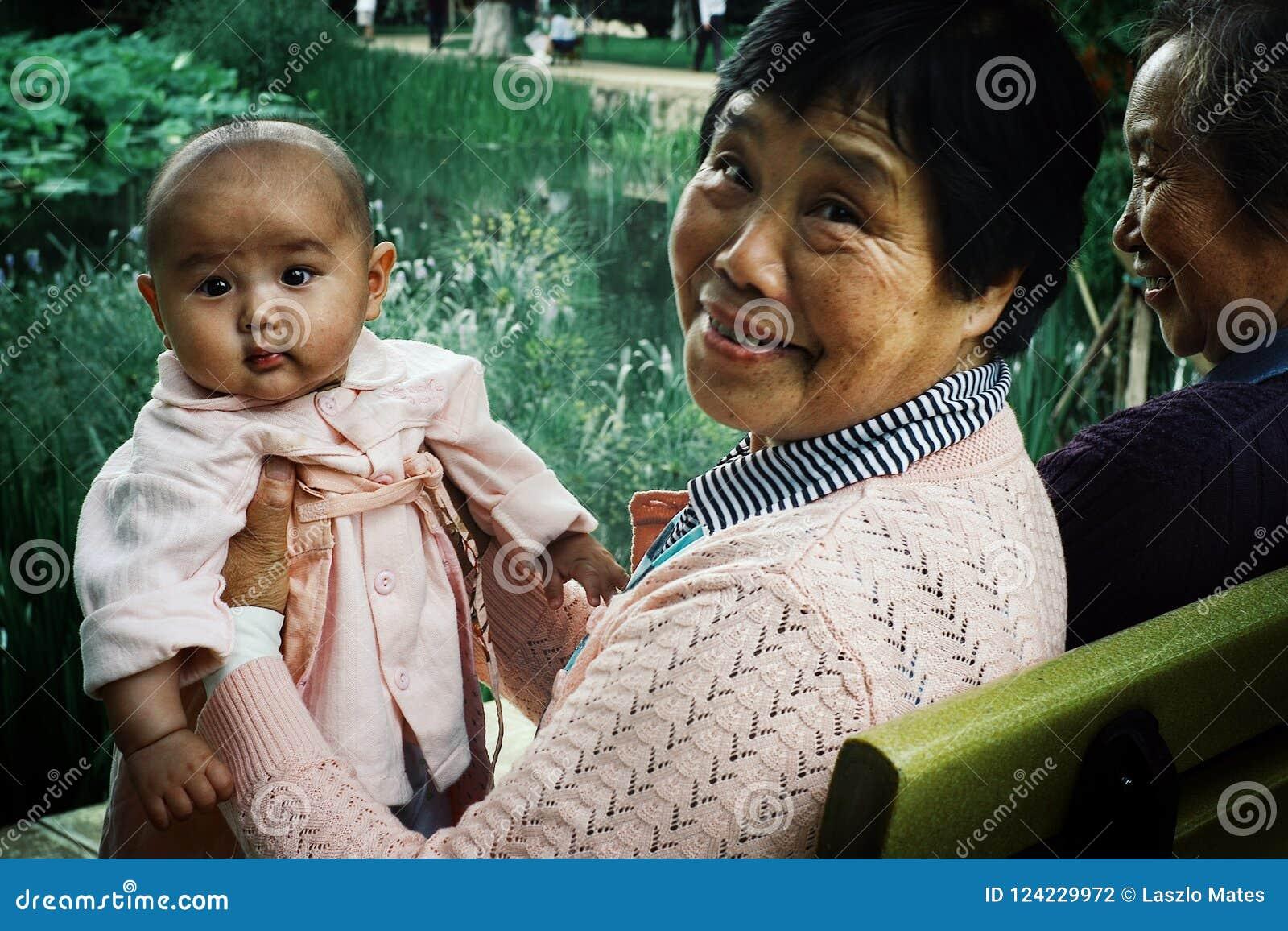 Grootmoeder met kleindochter in een park met vrienden