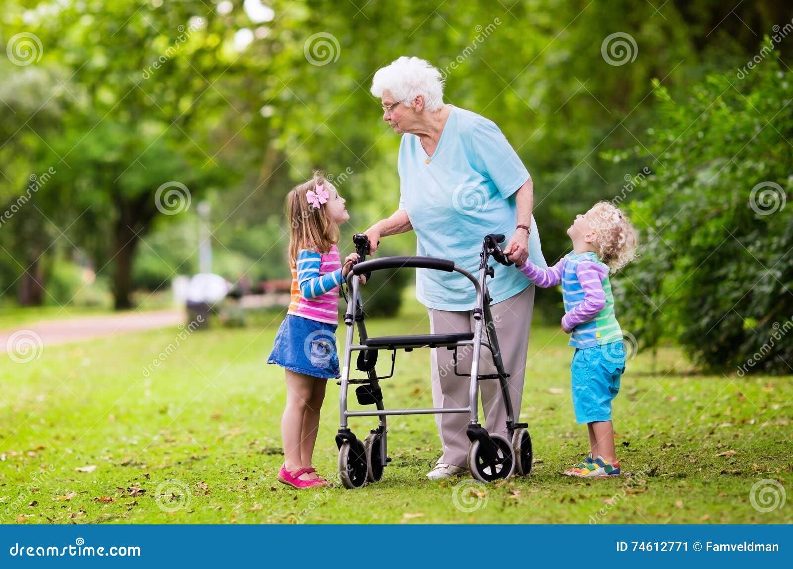 Grootmoeder met leurder het spelen met twee jonge geitjes
