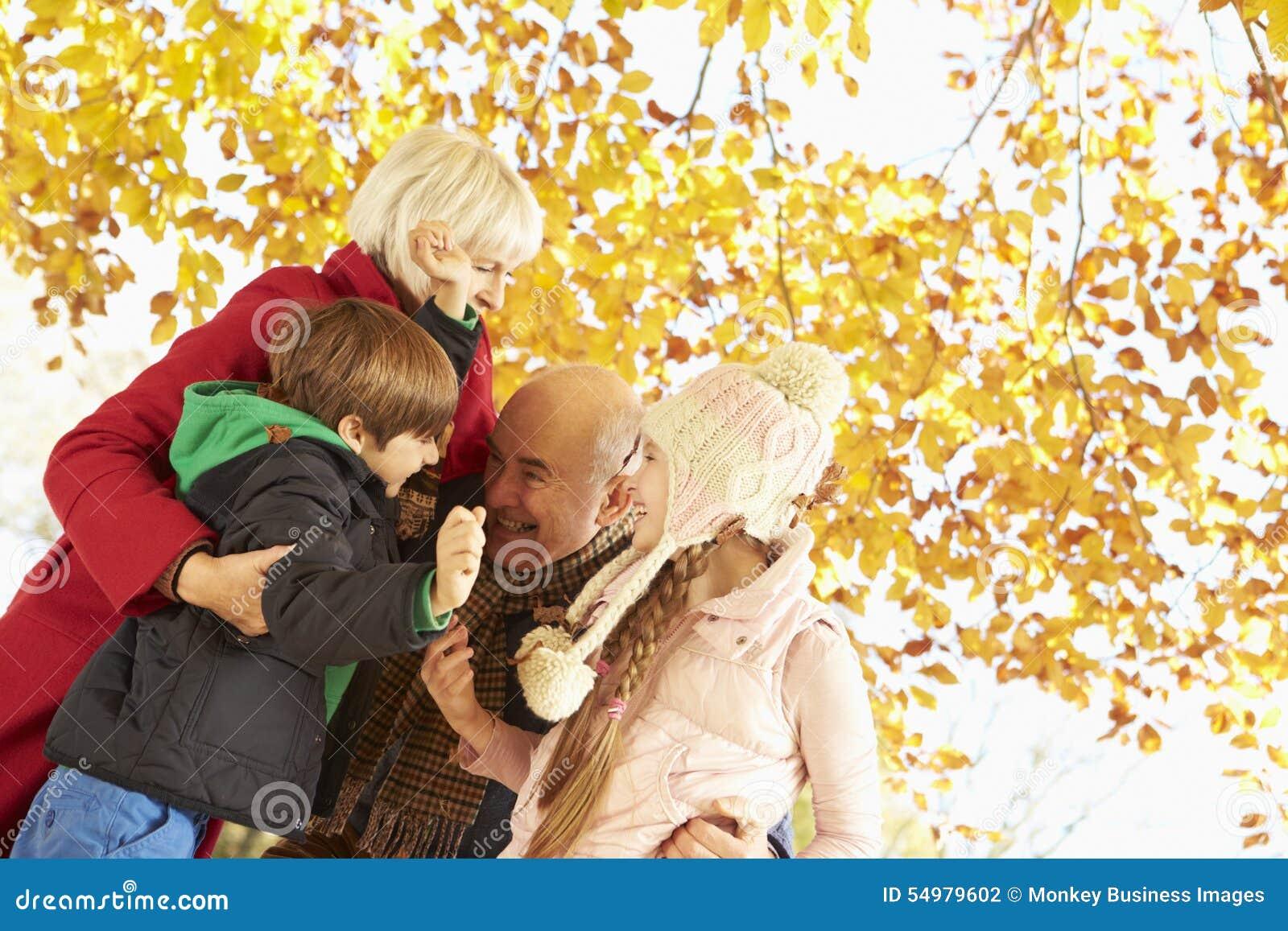 Grootouders en Kleinkinderen die onder Autumn Tree spelen
