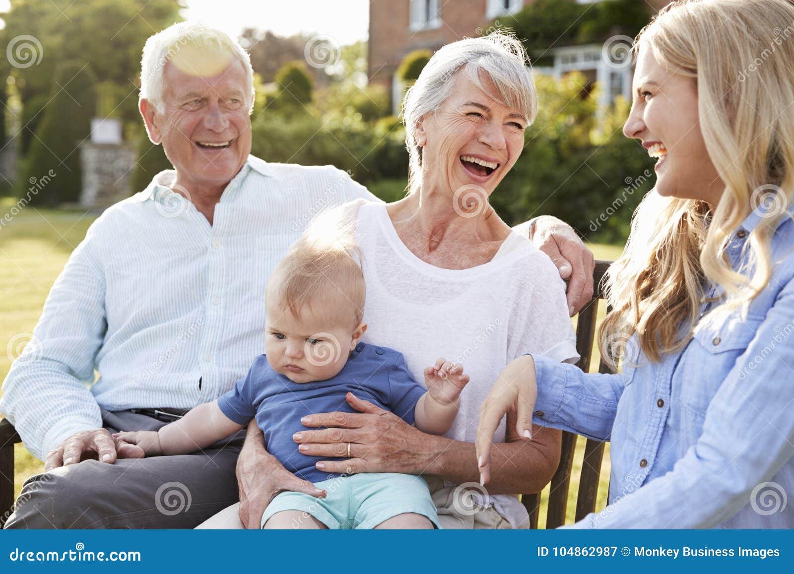 Grootouders Sit Outdoors With Baby Grandson en Volwassen Dochter