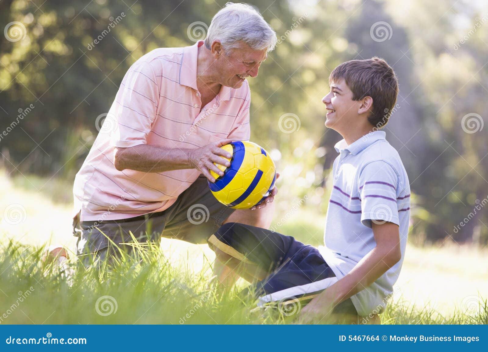 Grootvader en kleinzoon bij een park met een bal