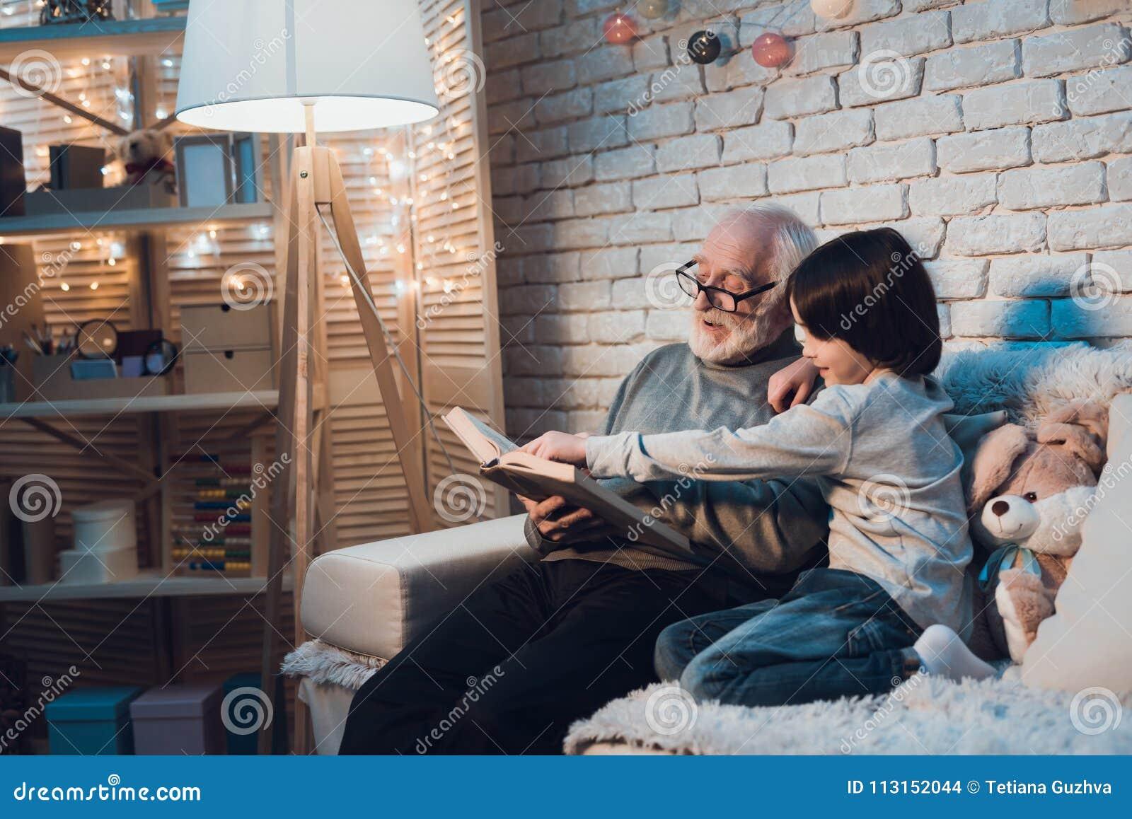 Grootvader en kleinzoon bij nacht thuis De opa leest sprookjesboek