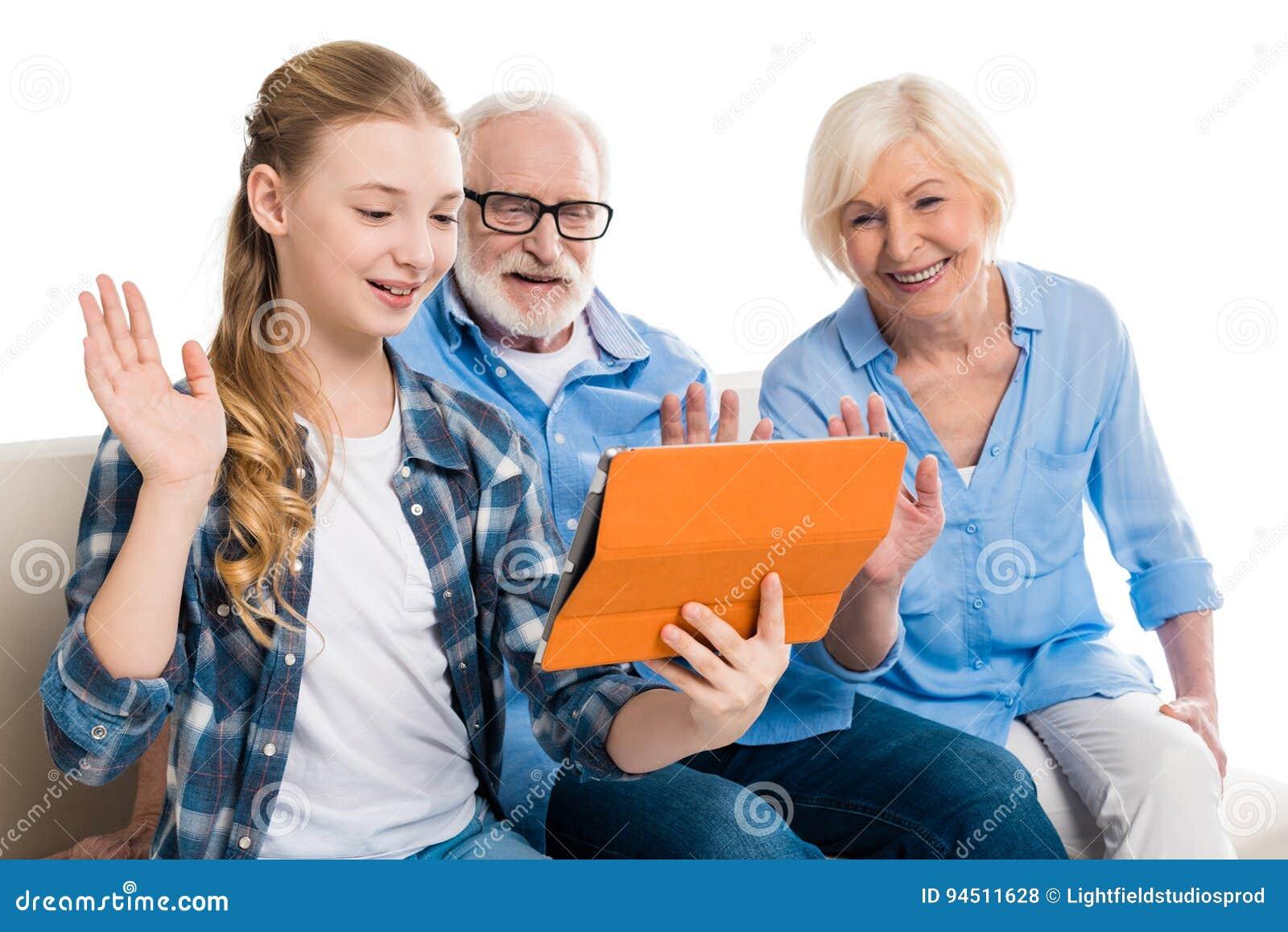 Grootvader, grootmoeder en kleinkind gebruikend digitale tablet en zittend op bank