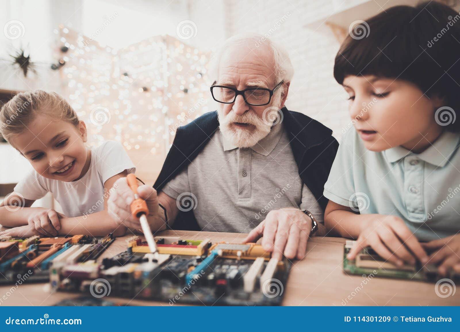 Grootvader, kleinzoon en kleindochter thuis De opa onderwijst kinderen hoe te solderen