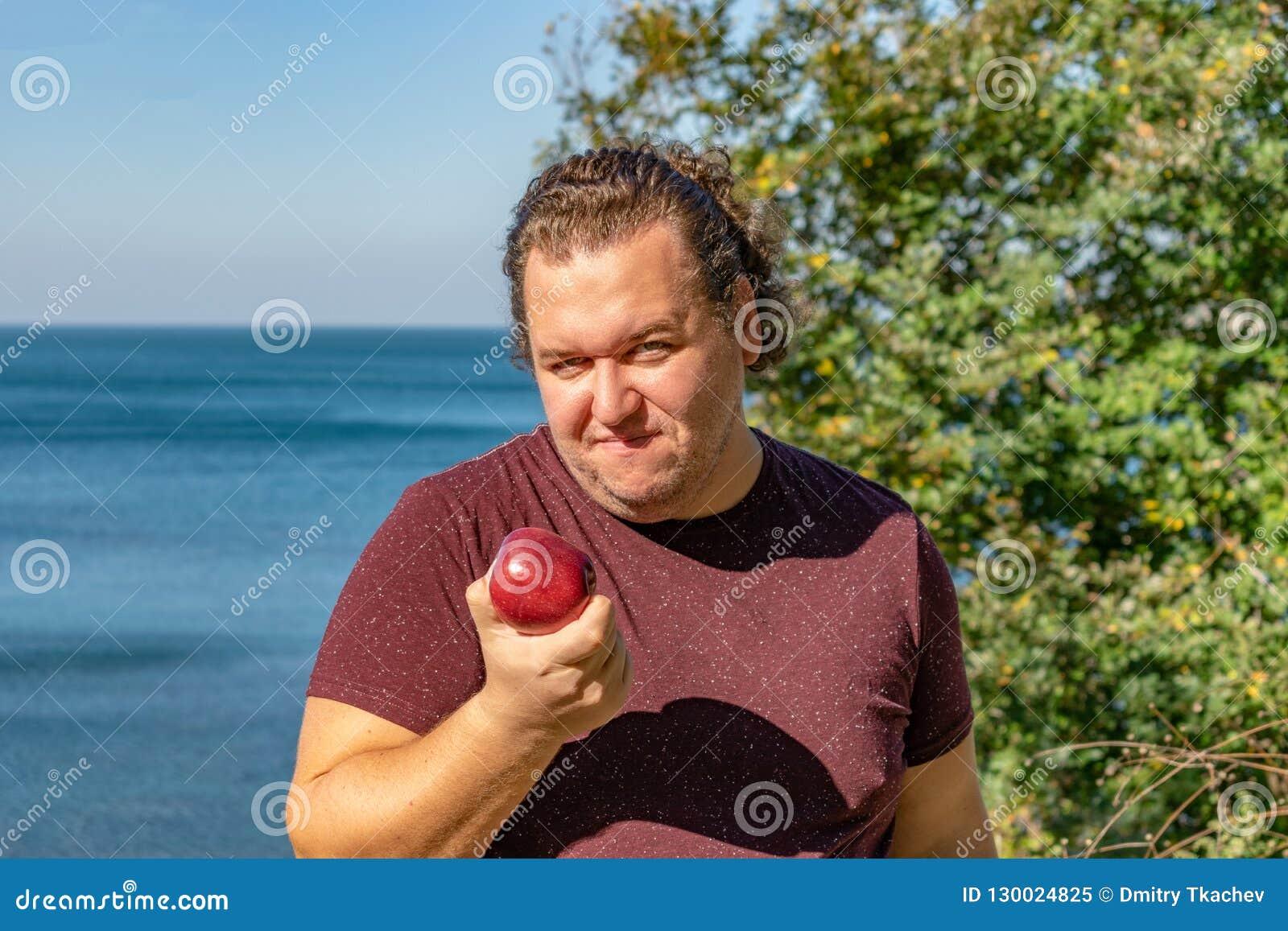 Gros homme drôle sur l océan mangeant des fruits Vacances, perte de poids et consommation saine