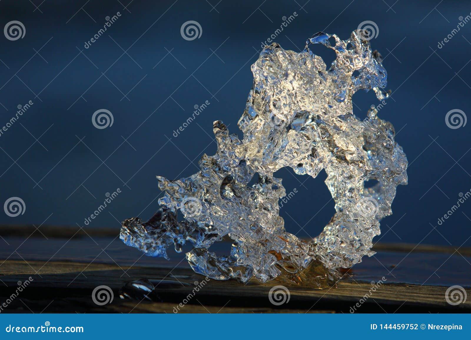 Gros morceaux comme un dragon de glace attrapés dans un lac au printemps contre une plage