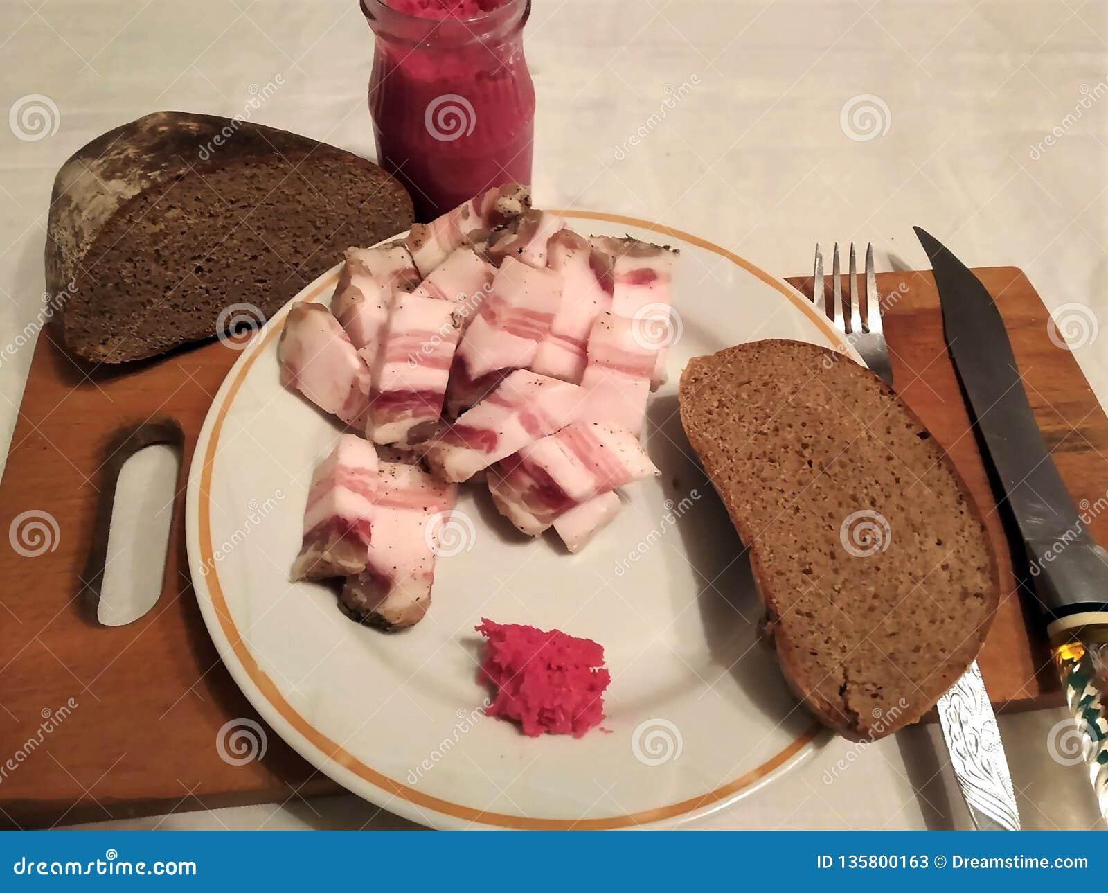 Gros salé est coupé par des morceaux d un plat avec le raifort et le pain sur une table pour de vrais hommes