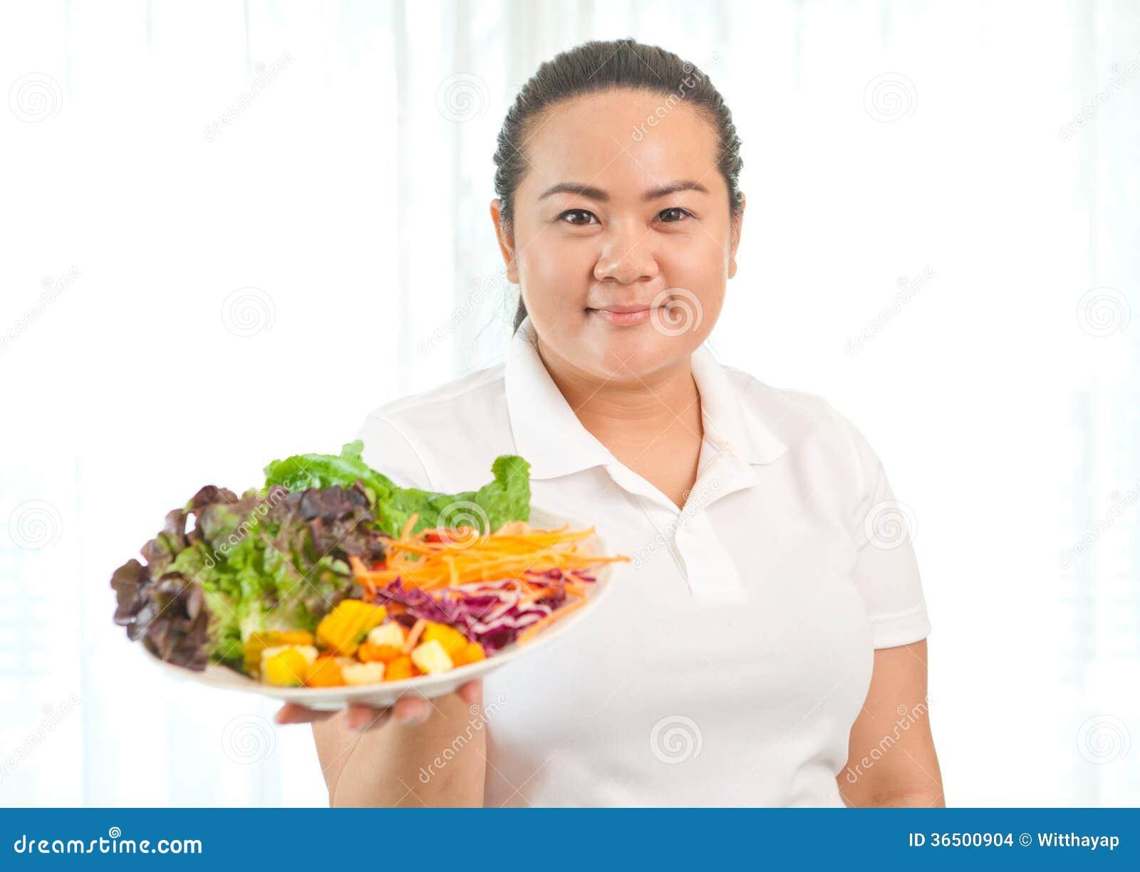 Grosse femme mangeant de la salade