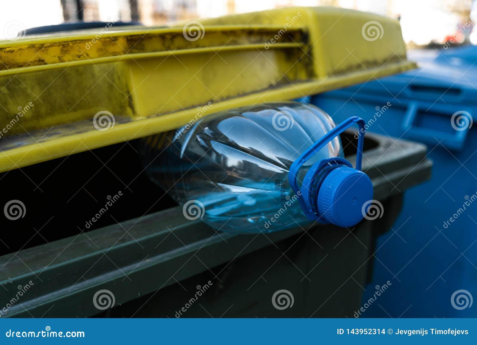 Grote blauwe plastic fles in een geelgroene afvalbak - recycleer voor aard