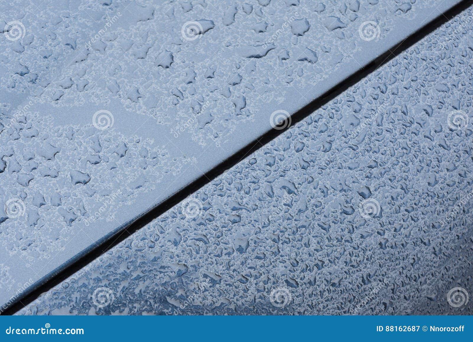 Grote dalingen van regen op de kap van een auto, verftextuur van een blauwe metaalverf