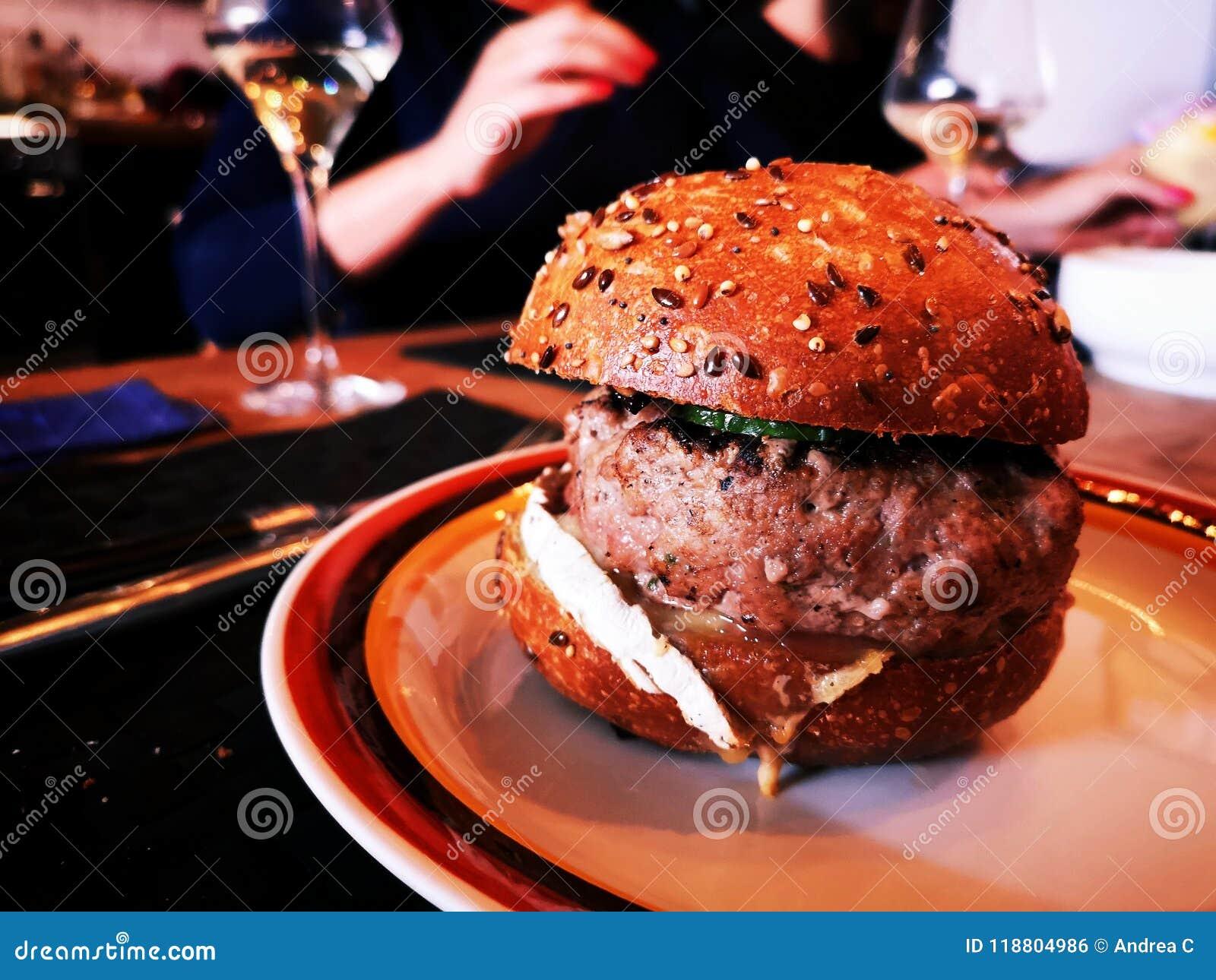 Grote eigengemaakte hamburger op plaat met vrouw op de achtergrond