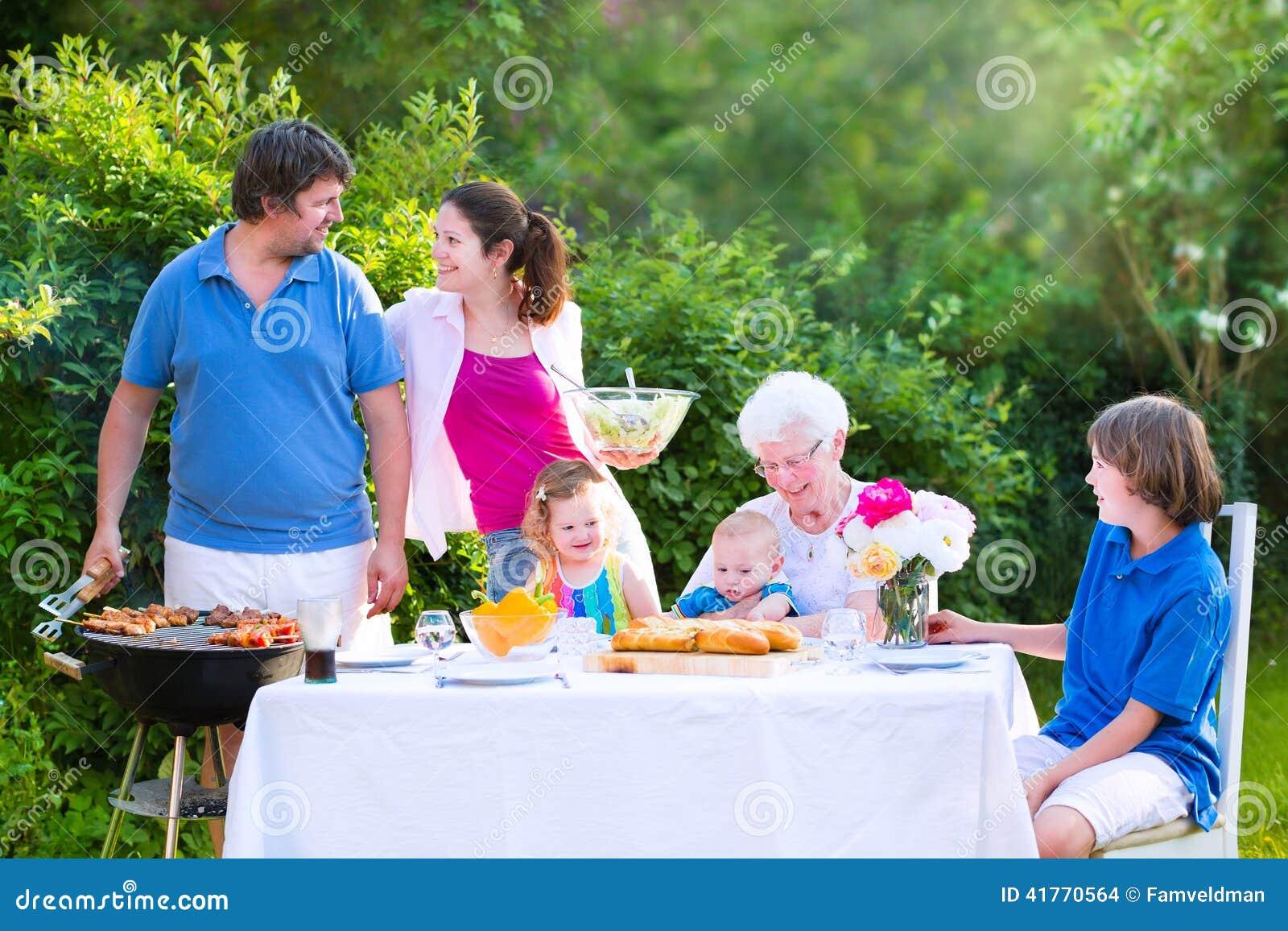 Grote familie die vlees voor lunch met grootmoeder roosteren