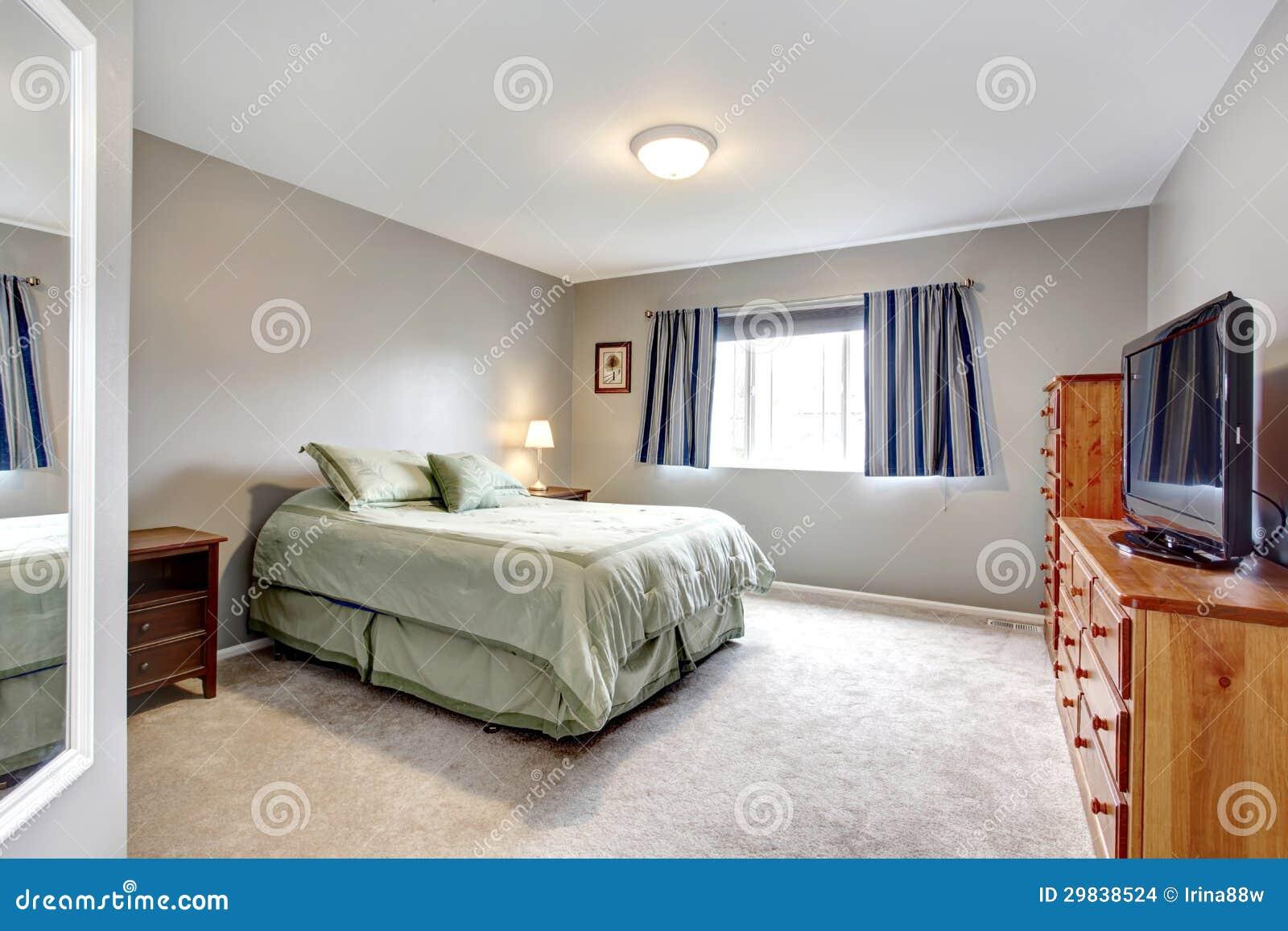 Grote grijze slaapkamer met opmaker tv en blauwe gordijnen stock afbeeldingen afbeelding - Grijze slaapkamer ...