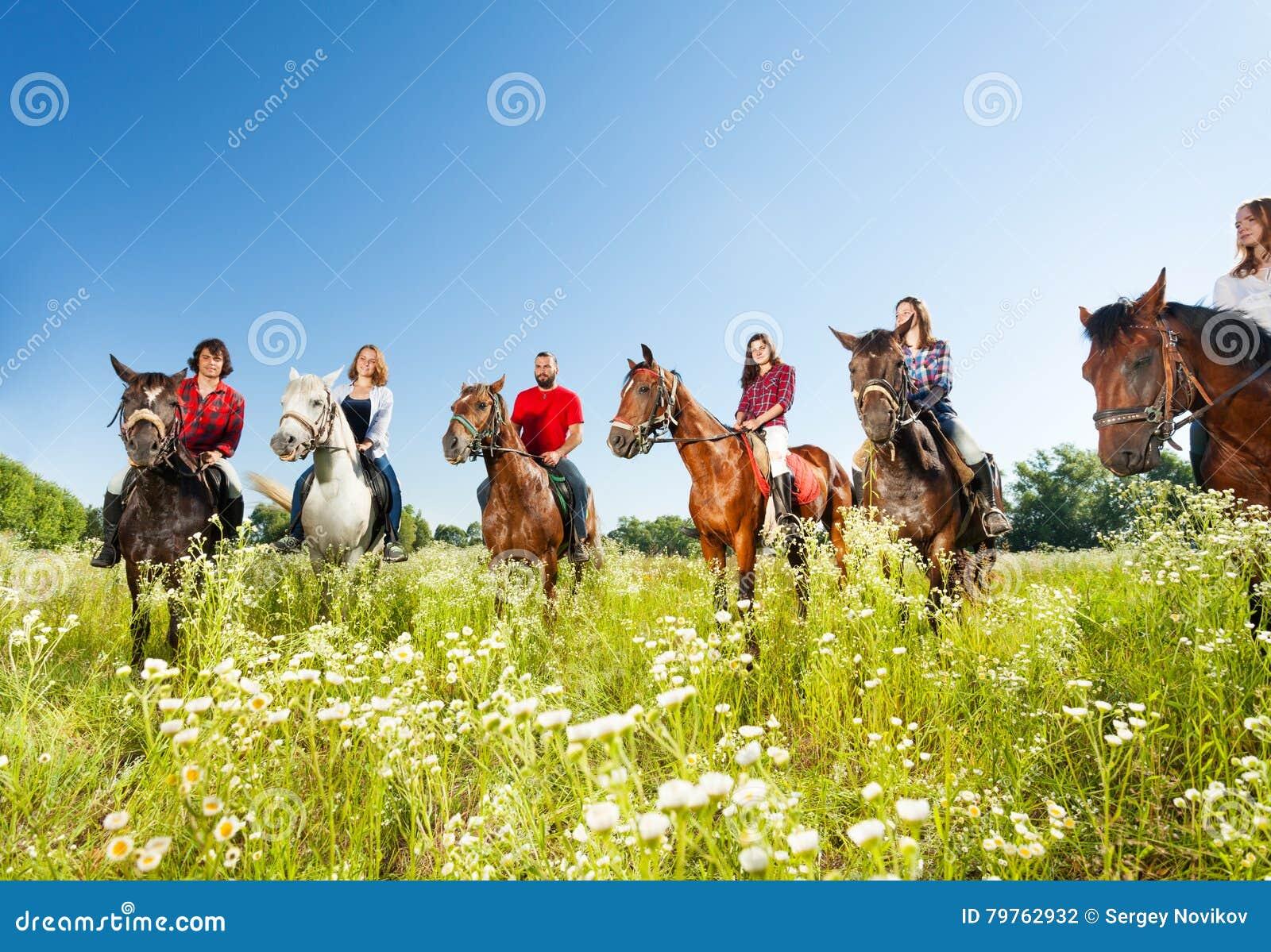 Grote groep horseback ruiters in bloemrijke weide
