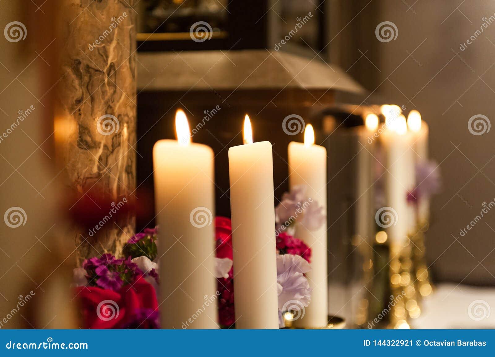 Grote kaarsen die in de kerk met vage achtergrond branden