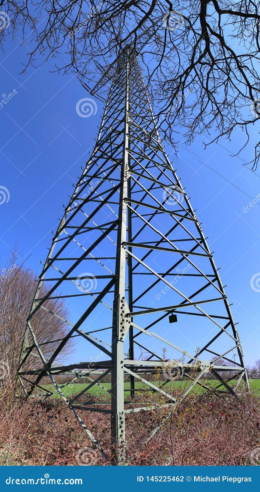 Grote machtspyloon die elektriciteit op een plattelandsgebied vervoeren