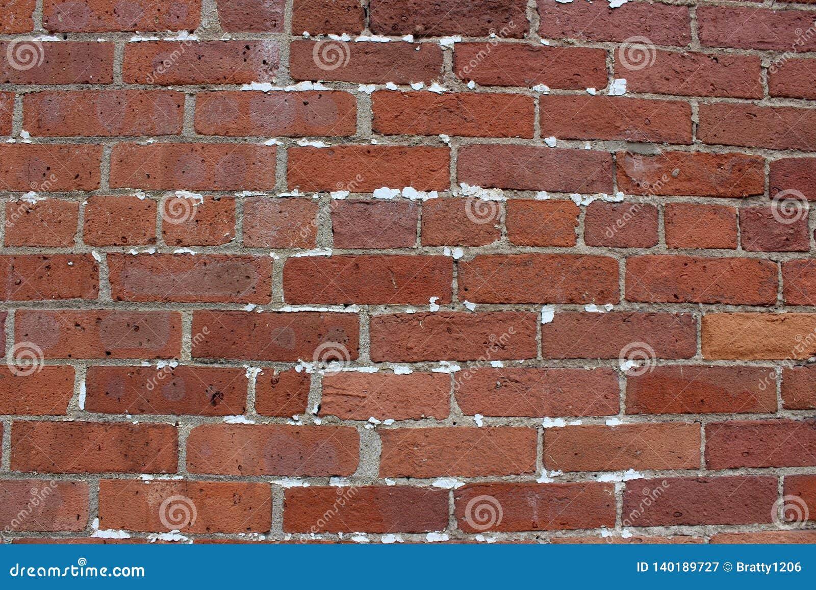 Grote muur rode en bruine bakstenen met tekens van reparatie en helemaal het herstellen