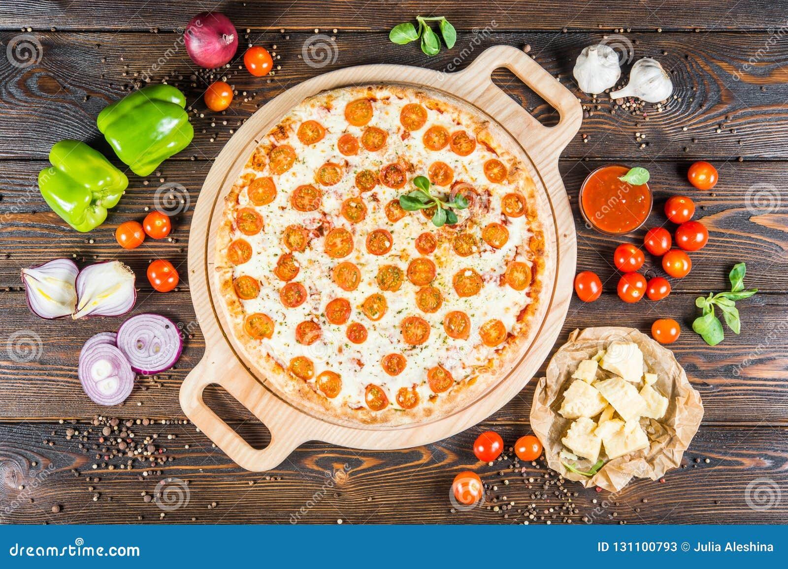 Grote pizza 'Margarita 'met kaas en tomaten om scherpe raad op een donkere houten achtergrond ingrediënten