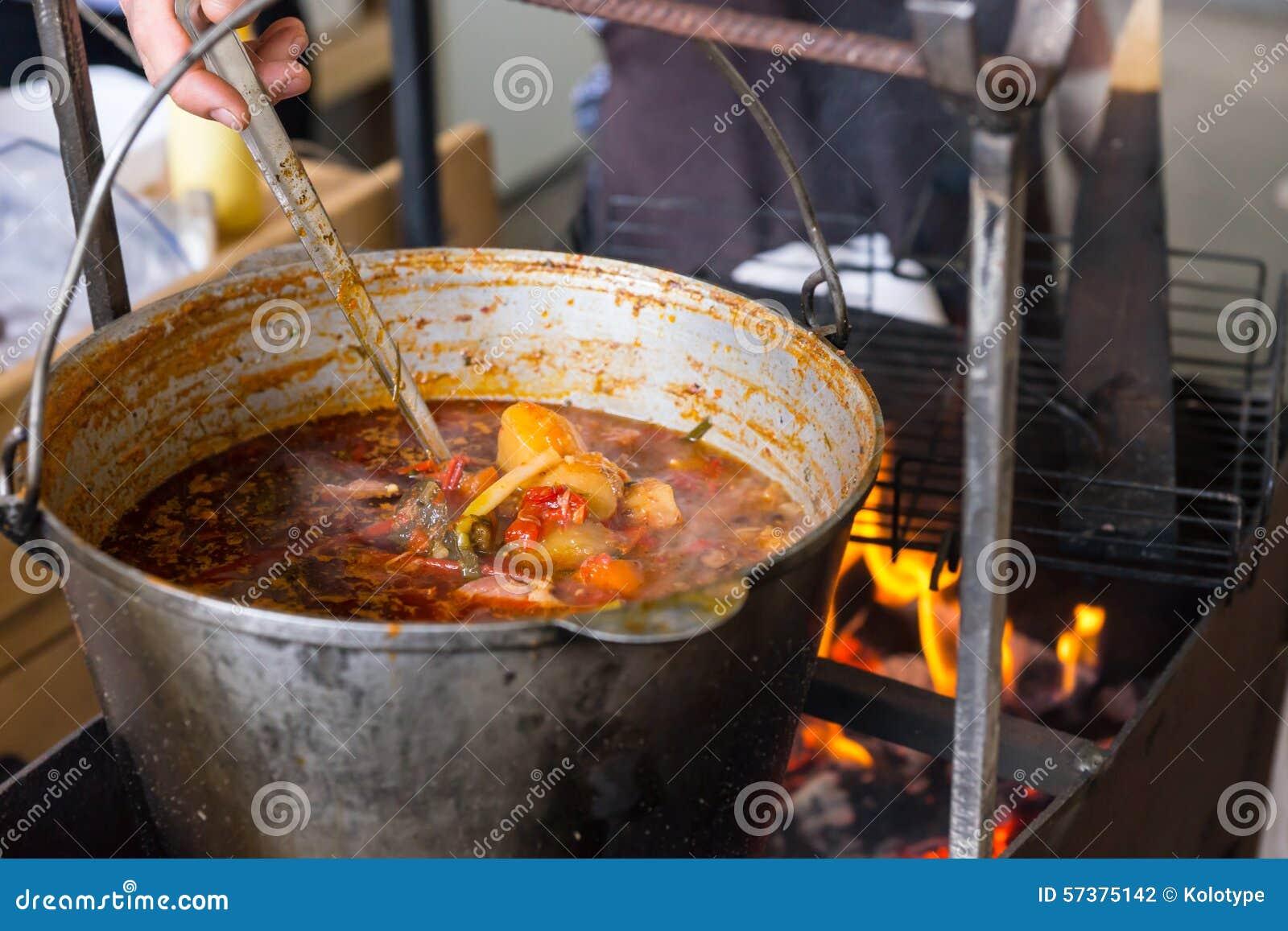 Grote pot die van hutspot over een brand sudderen