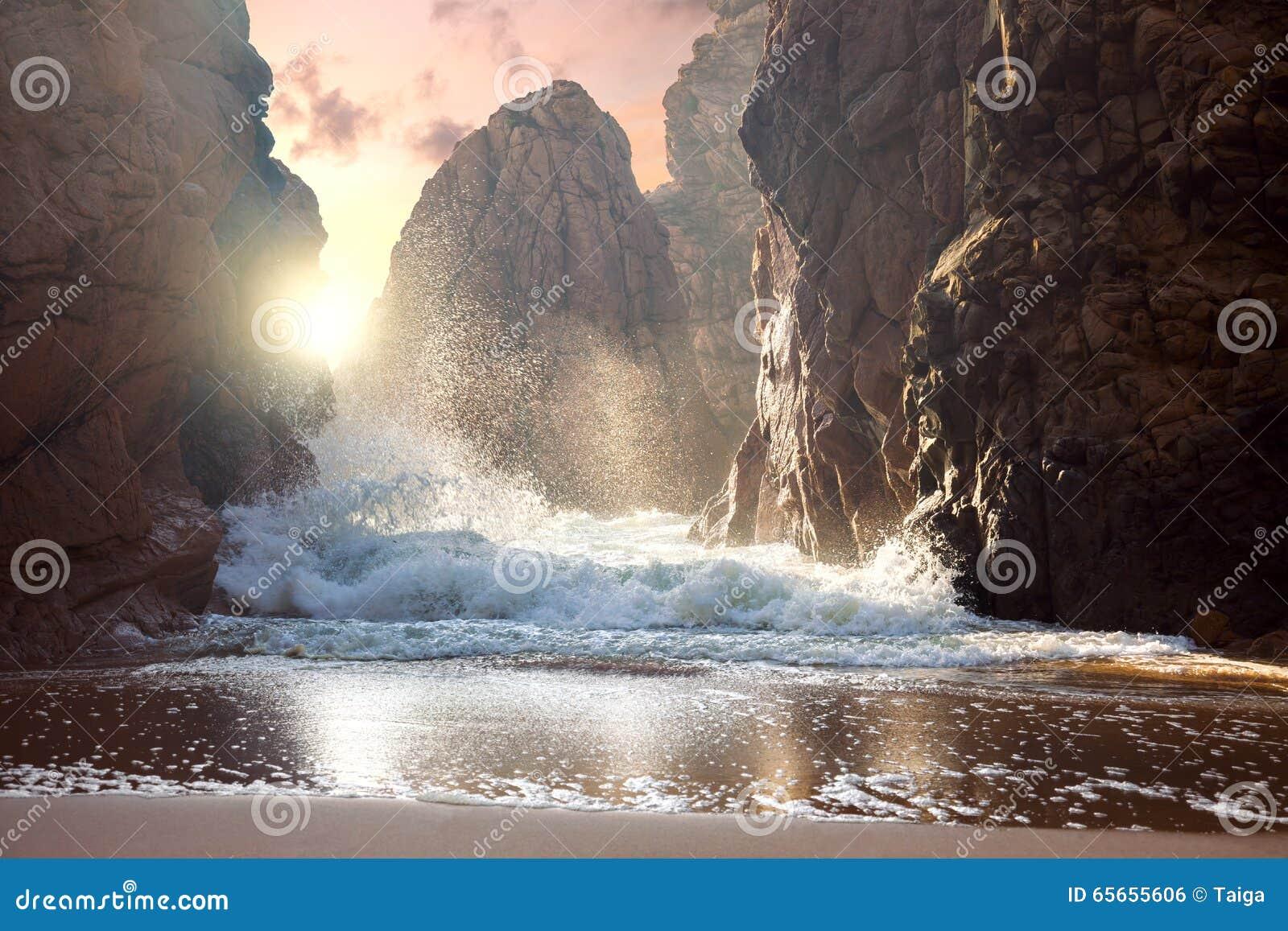 Grote rotsen en oceaangolven bij zonsondergang