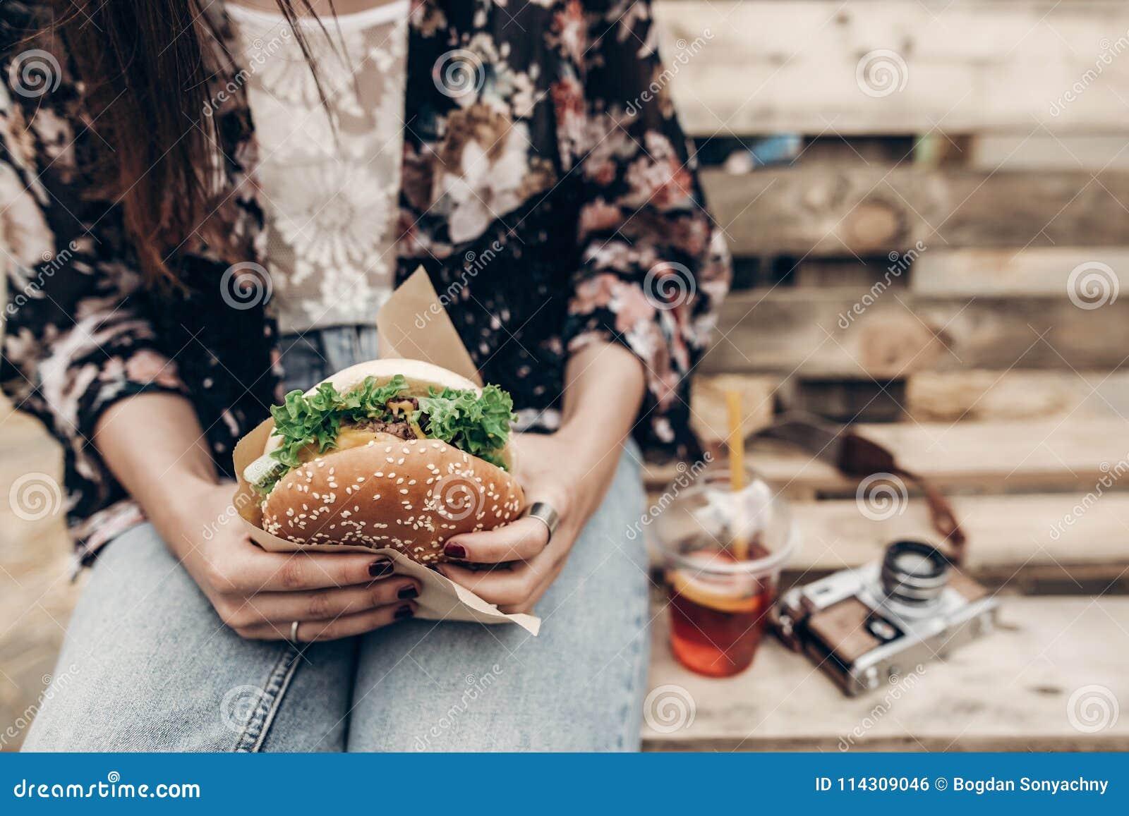 Grote sappige hamburger ter beschikking modieuze hipstervrouw die yummy CH houden