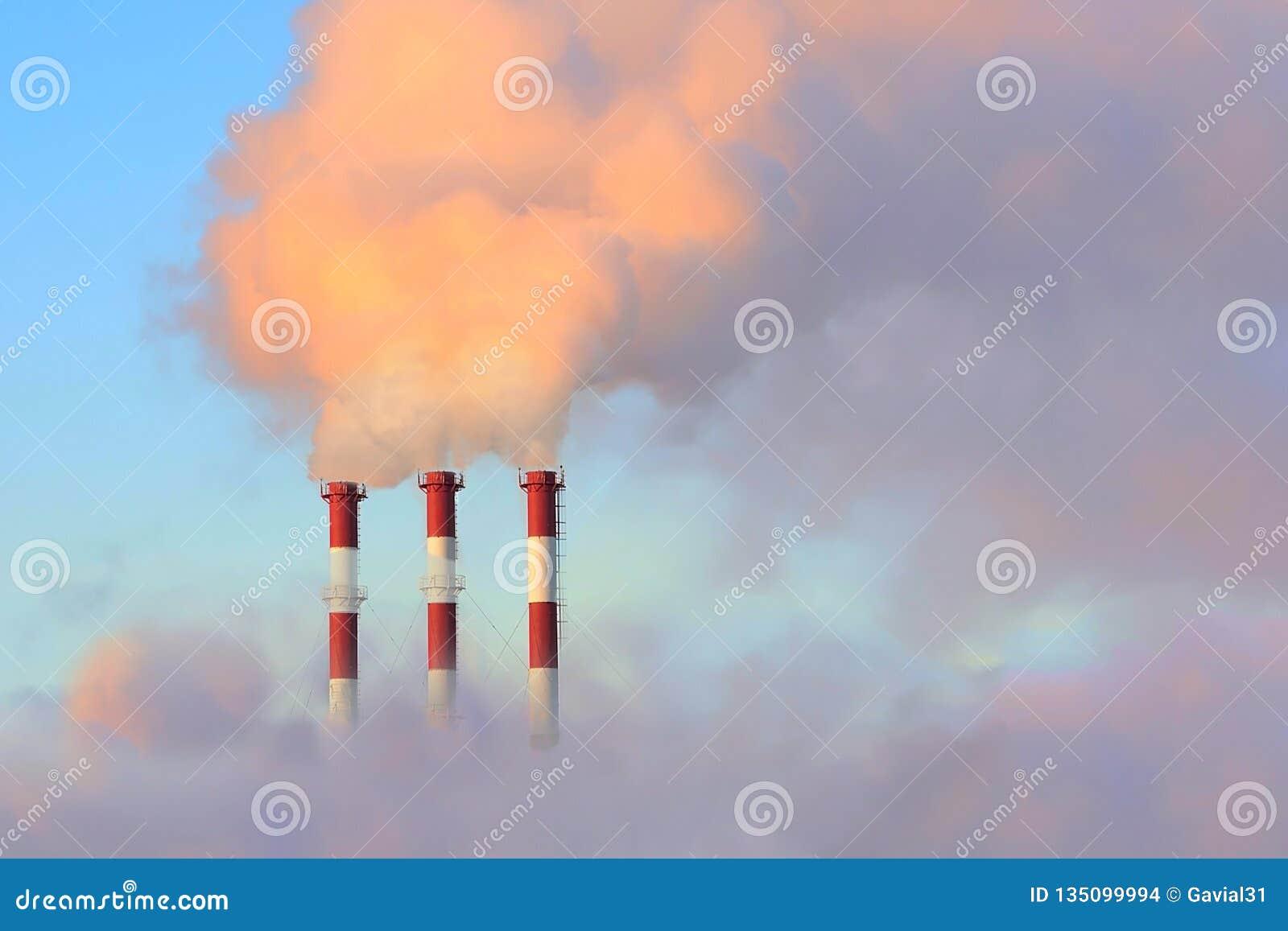 Grote schoorsteen drie tegen de hemel en de rook