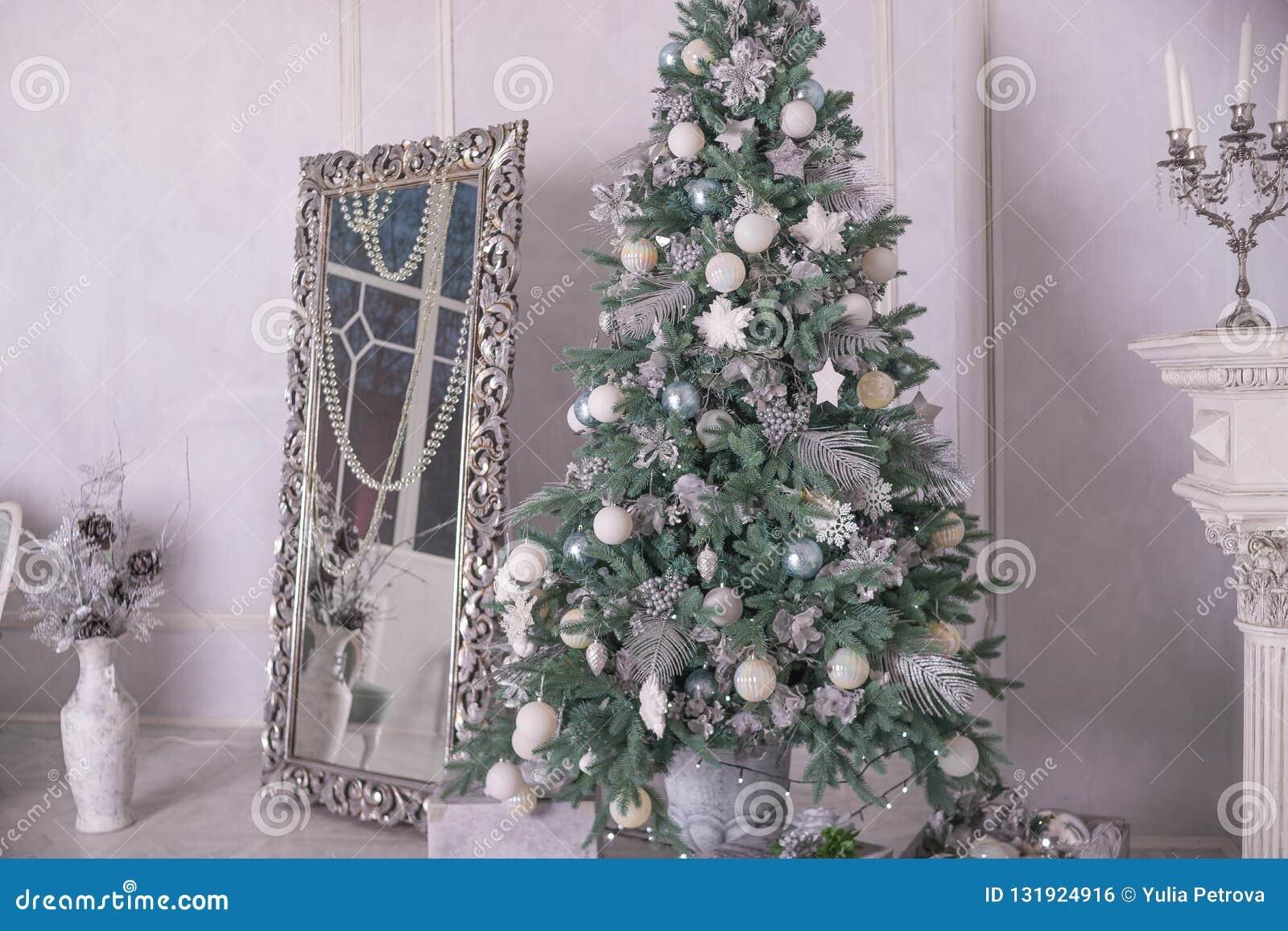 Grote zilveren en witte verfraaide Kerstmisboom met giften in luxebinnenland Nieuwjaar thuis Kerstmisbinnenland met