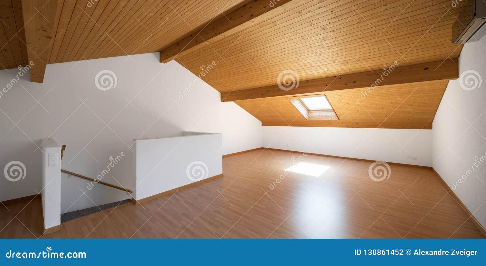 Grote zolder met houten vloeren en blootgestelde stralen