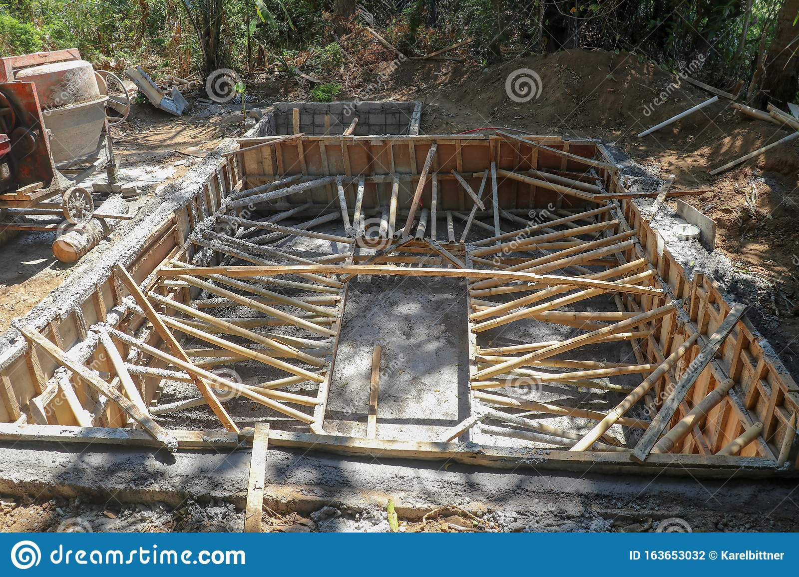 The Ground Recessed Pool In The Process Of Construction Masonry Formwork Reinforced With Bamboo Trunks Excavated Clay Piled Up Stock Photo Image Of Cement Modern 163653032