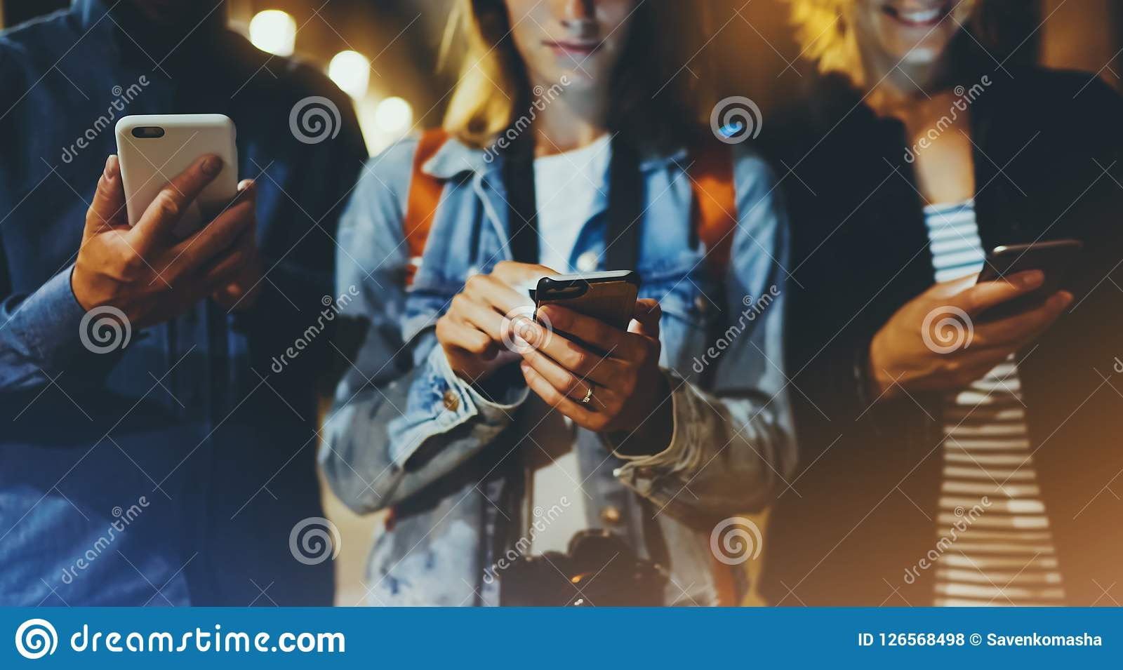Group adult hipsters friends using in hands mobile phone closeup, street online wi-fi internet concept, bloggers together pointing