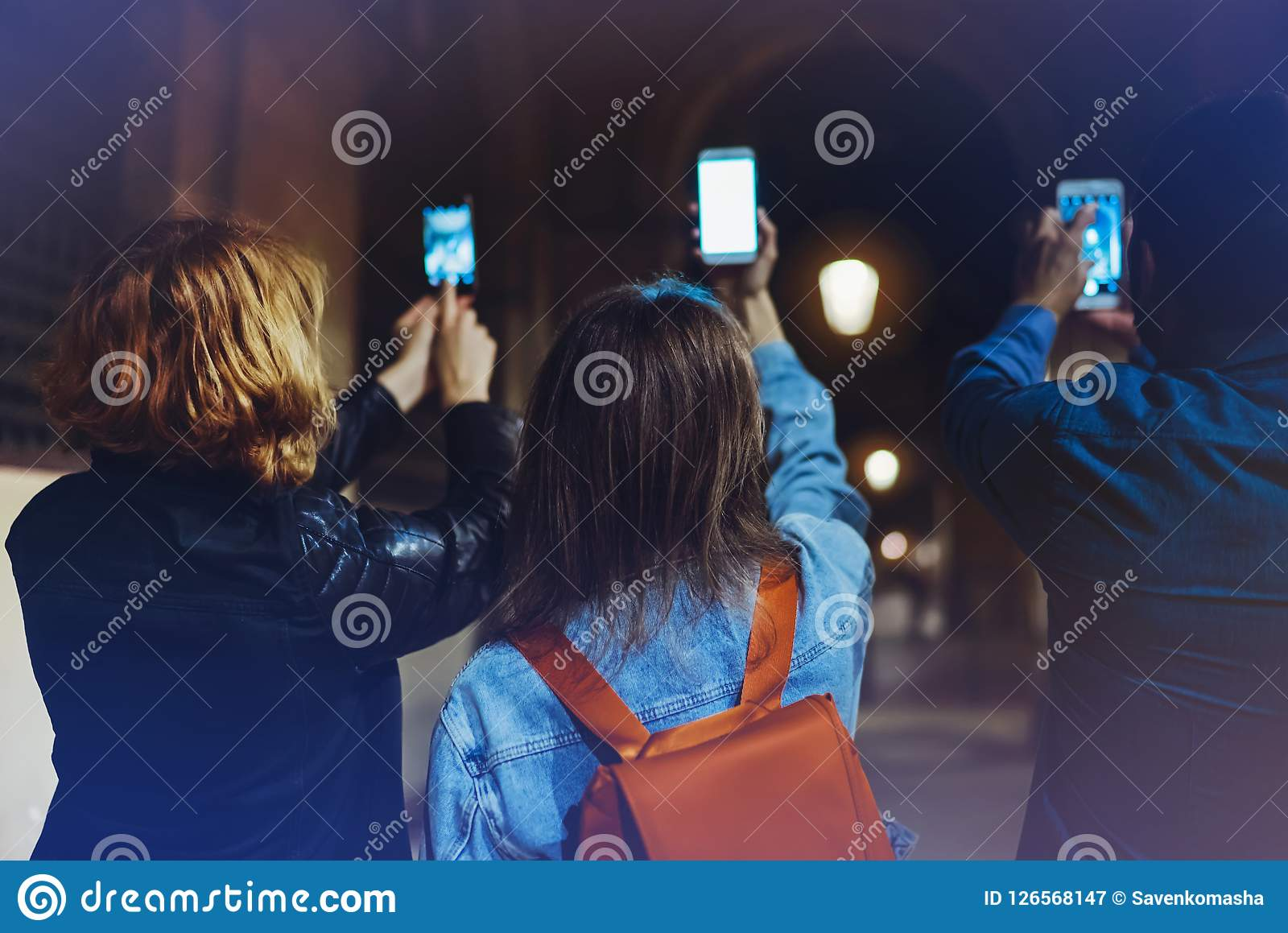 Group adult hipsters using in hands mobile phone closeup, street online wi-fi internet concept, bloggers friends together