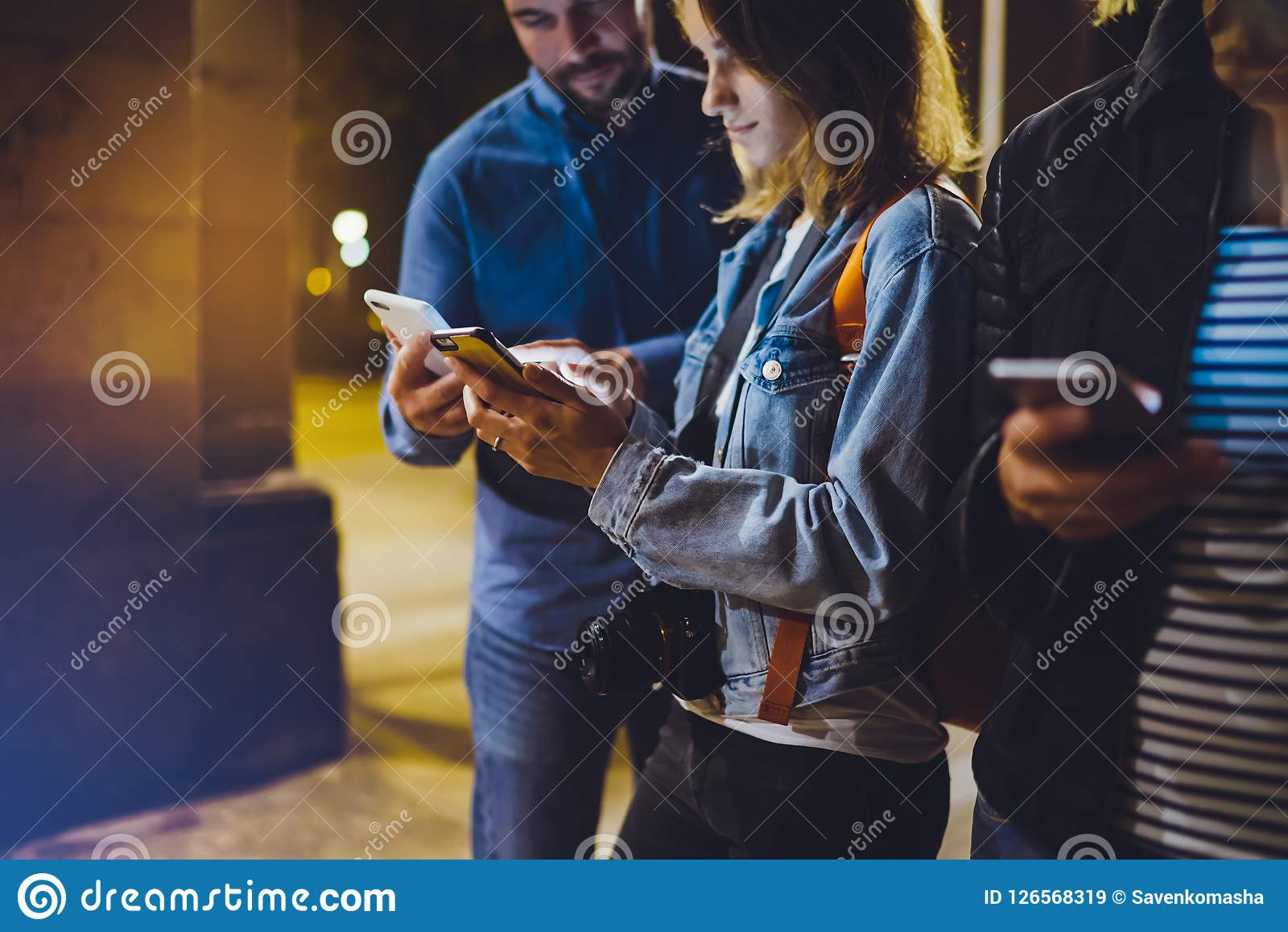 Group adult hipsters using in hands mobile phone closeup, street online wi-fi internet concept, bloggers friends together pointing
