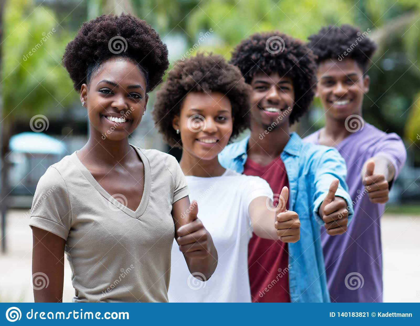 Group of african american young adults showing thumb up