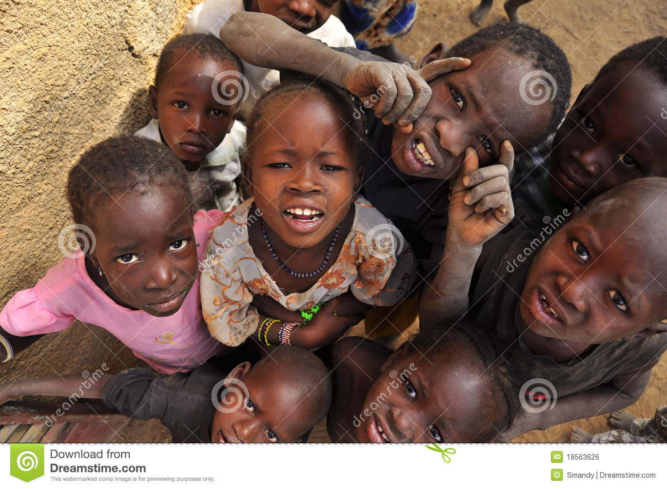 Group of black children making faces and looking curious in a village of niger west africa