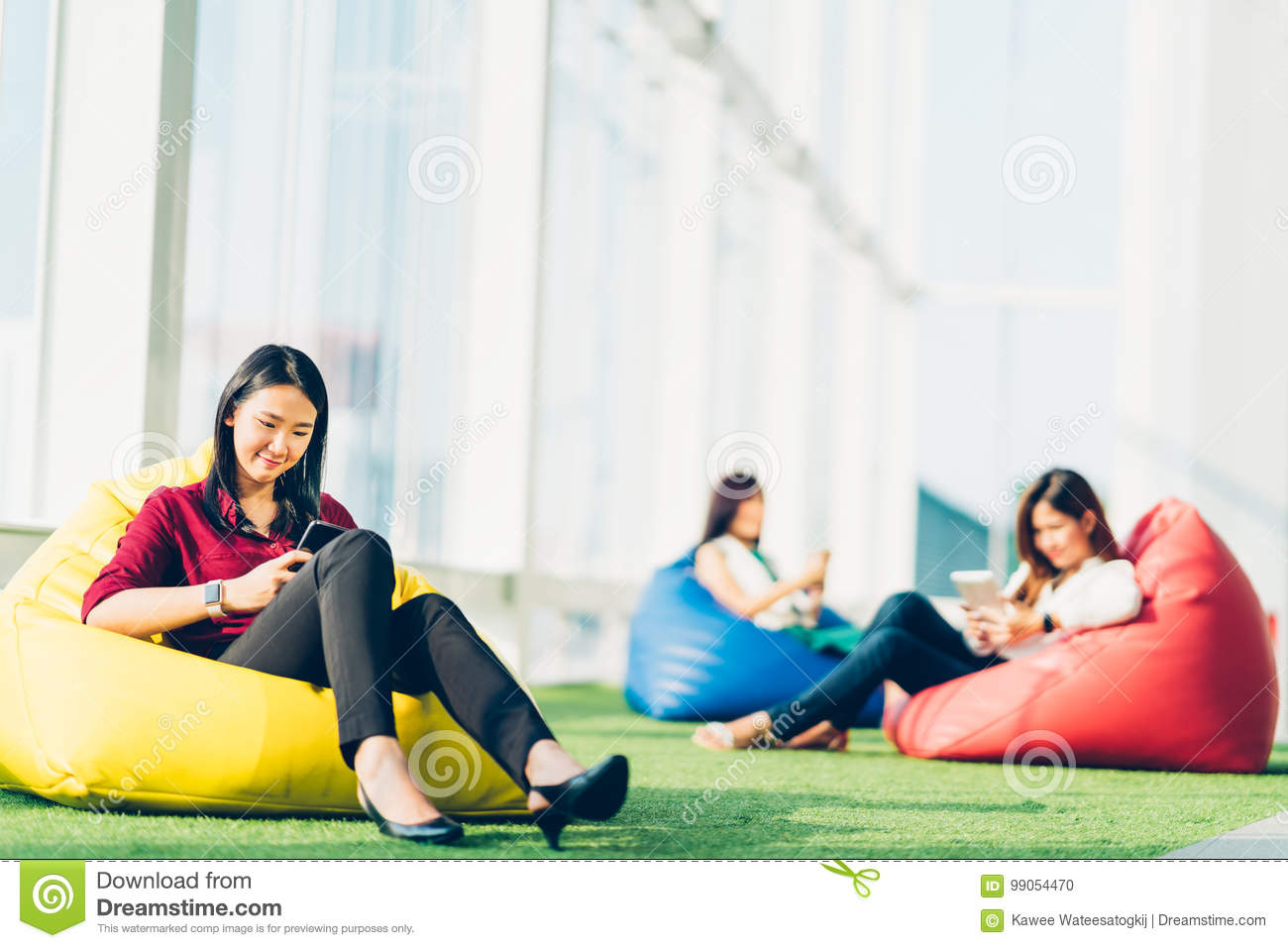 Group of Asian college student or business colleague using smartphone sit together in modern office or university campus