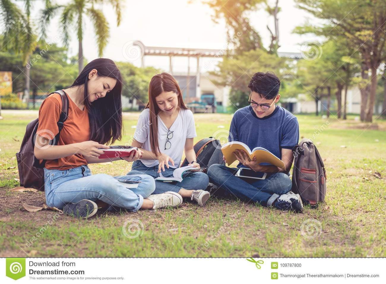 Group of Asian college student reading books and tutoring special class for exam on grass field at outdoors. Happiness and