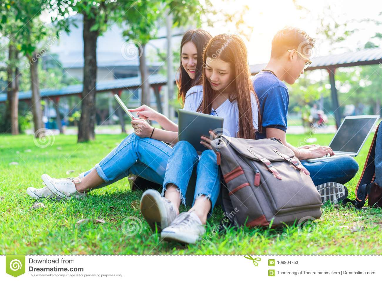 Group of Asian college student using tablet and laptop on grass