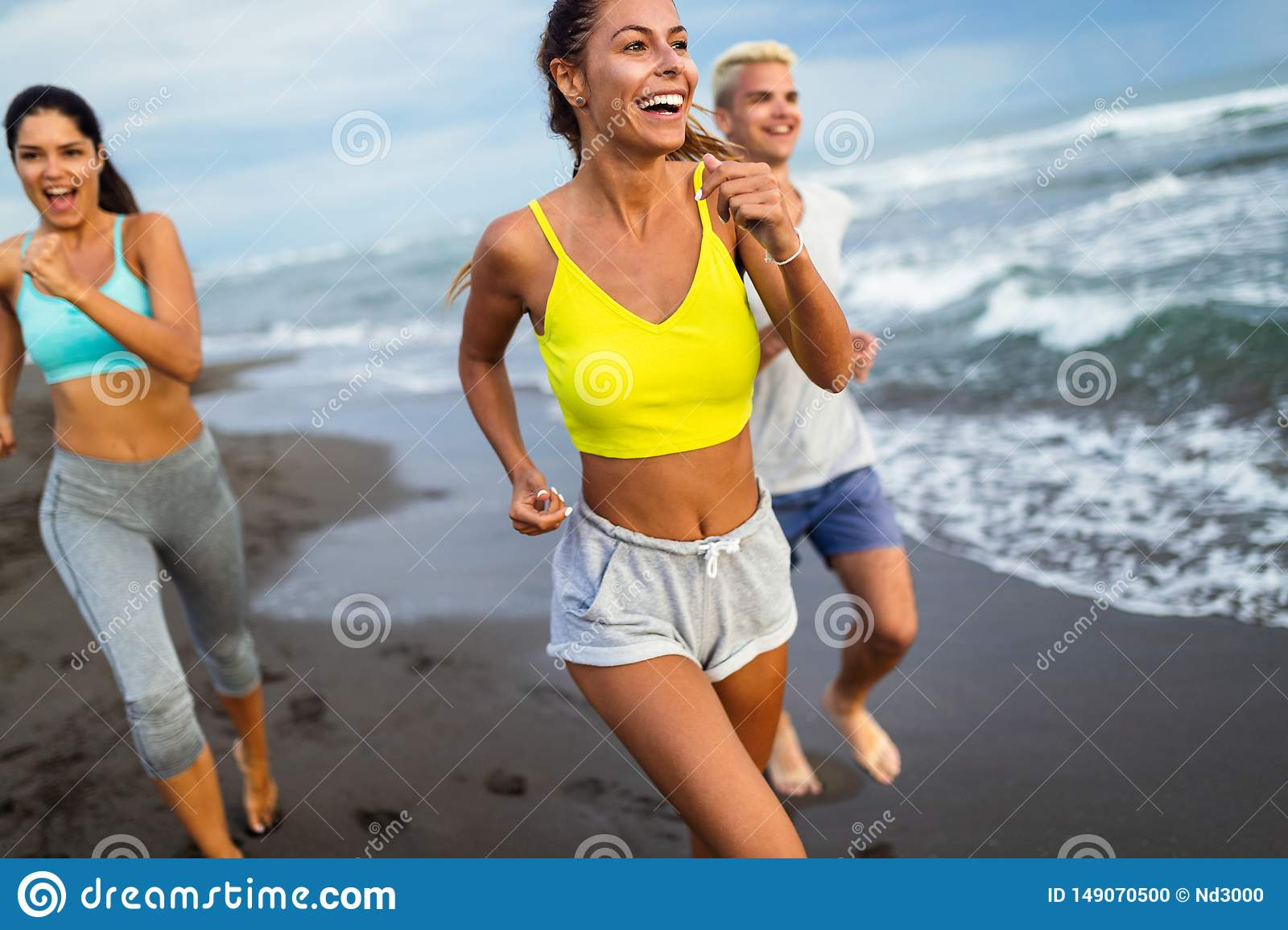 Group of athletes running on ocean front. Friends in sportswear training together outdoors.