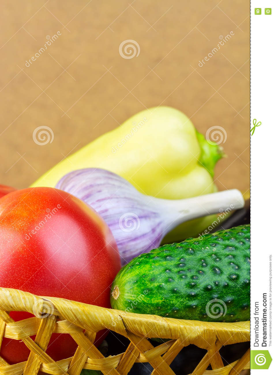 group of backyard vegetables in wicker basket on wooden background