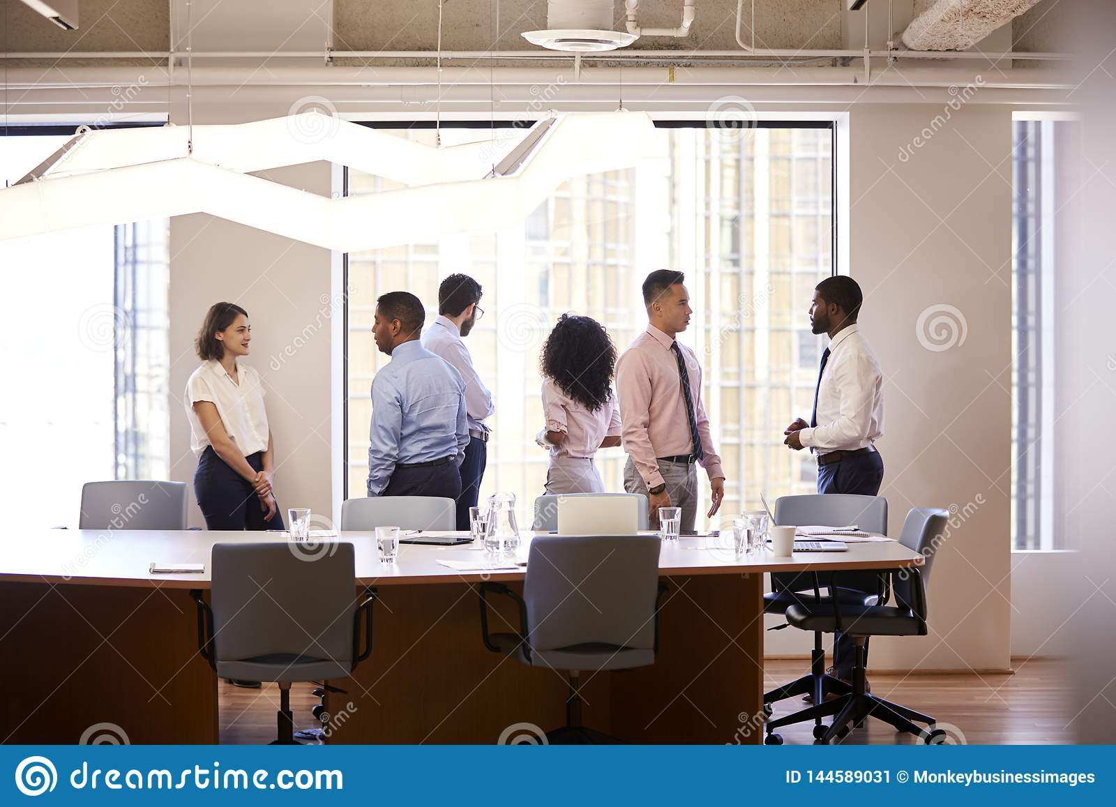 Group Of Business Colleagues Chatting In Office After Meeting