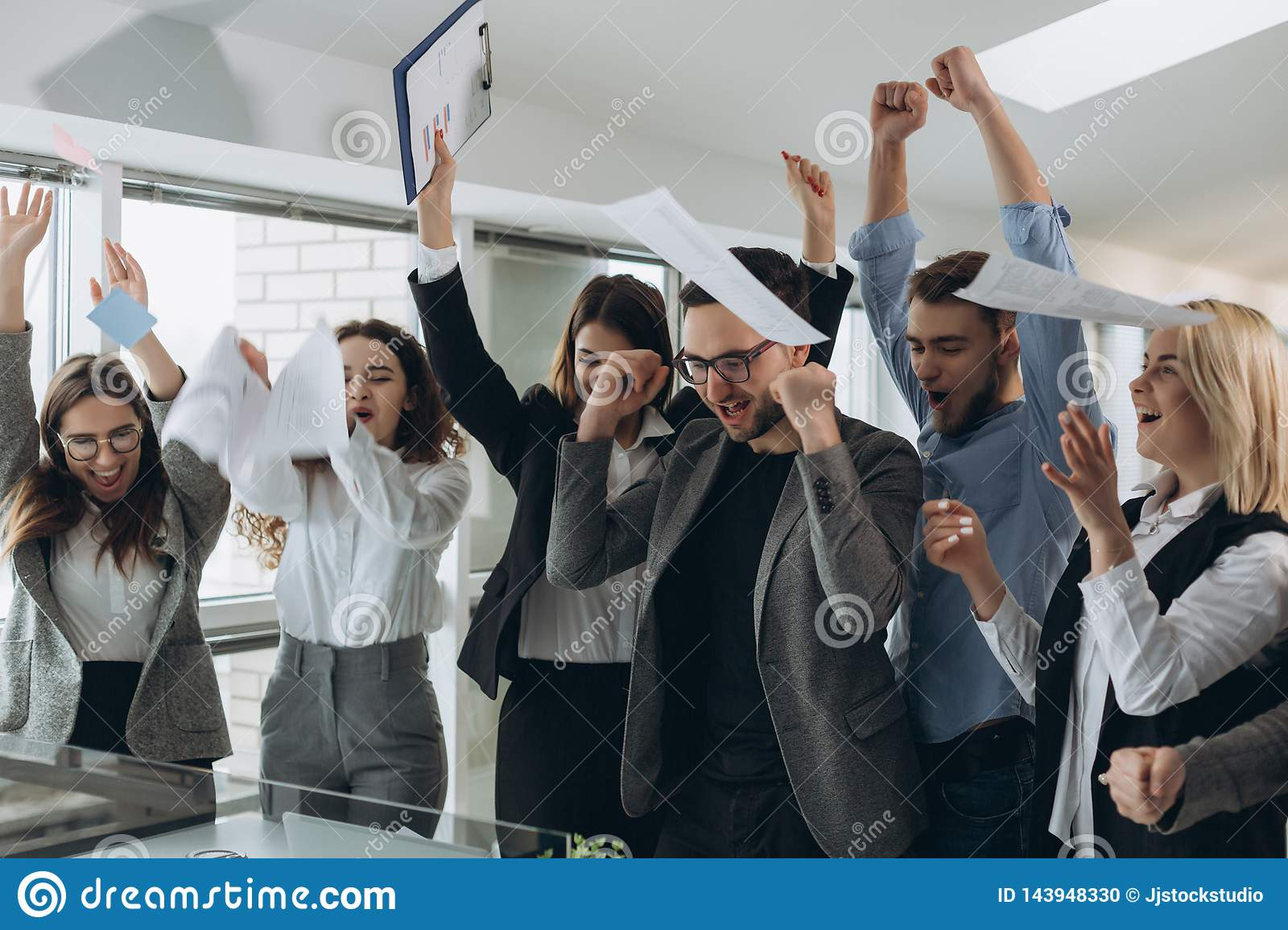 Group of business people celebrating by throwing their business papers and documents fly in air, Power of cooperation, Success