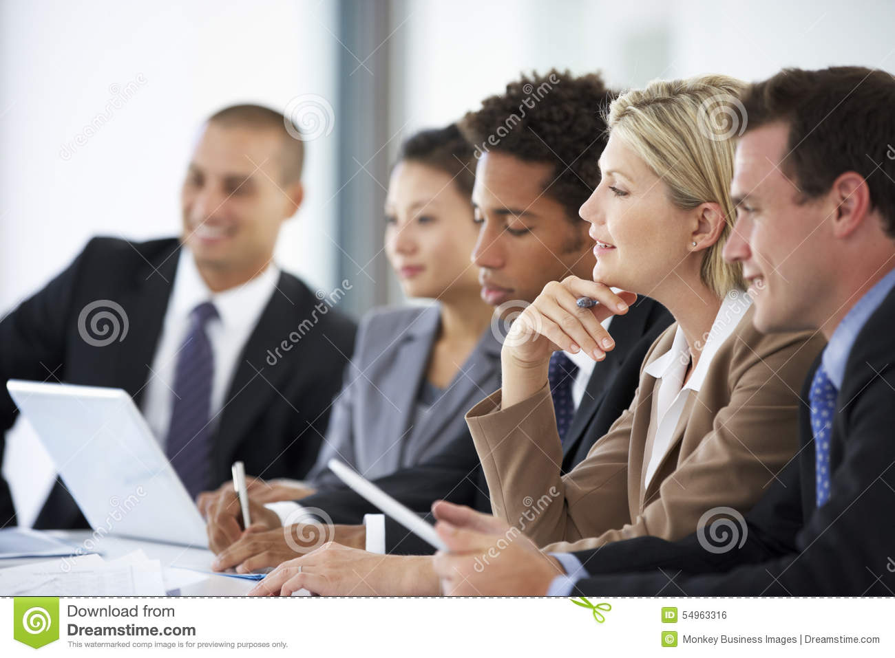 Group Of Business People Listening To Colleague Addressing Office Meeting
