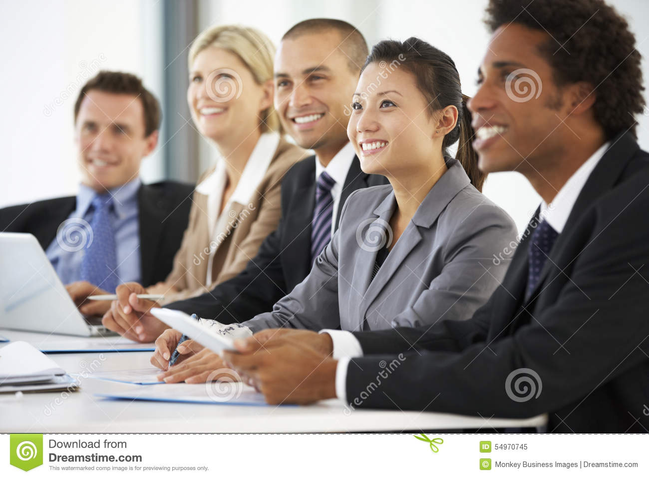 Group Of Business People Listening To Colleague Addressing Office