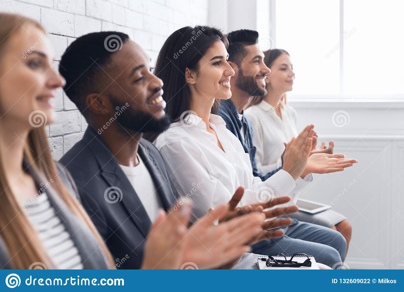 Group of businesspeople clapping hands at meeting