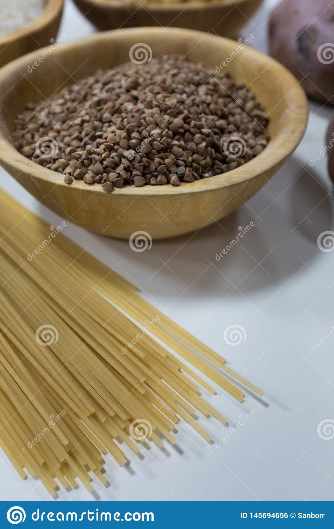 Group of carbohydrates for diet - bread, rice, potatoes and pasta on a wood table in the background